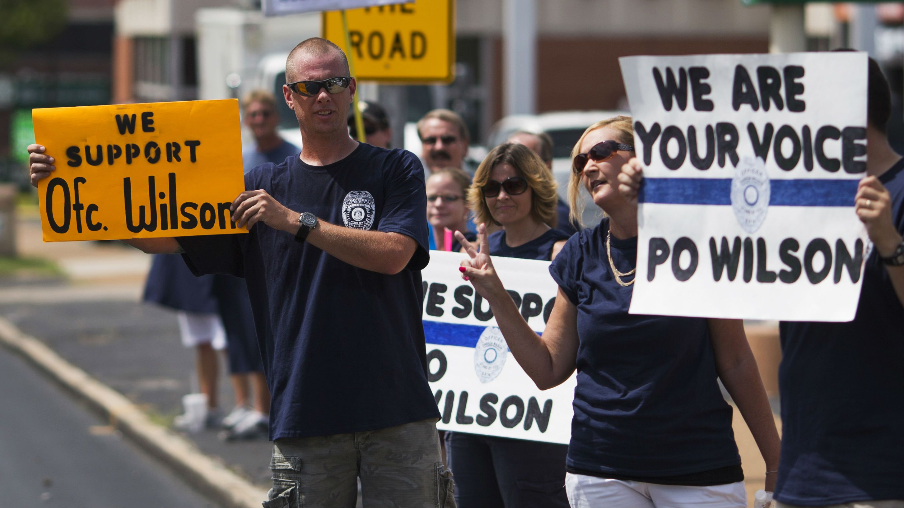 Supporters of officer Darren Wilson hold placards outside Barney's Sports Pub in St. Louis, Missouri August 23, 2014. No arrests were recorded overnight, marking three consecutive relatively calm nights for the St. Louis suburb following daily unrest since Michael Brown, 18, was shot by Ferguson officer Darren Wilson on Aug. 9. About 14 miles (22 km) away in St. Louis, dozens of supporters of the officer gathered at Barney's Sports Pub to raise money for Wilson's family. REUTERS/Adrees Latif (UNITED STATES - Tags: CRIME LAW CIVIL UNREST)
