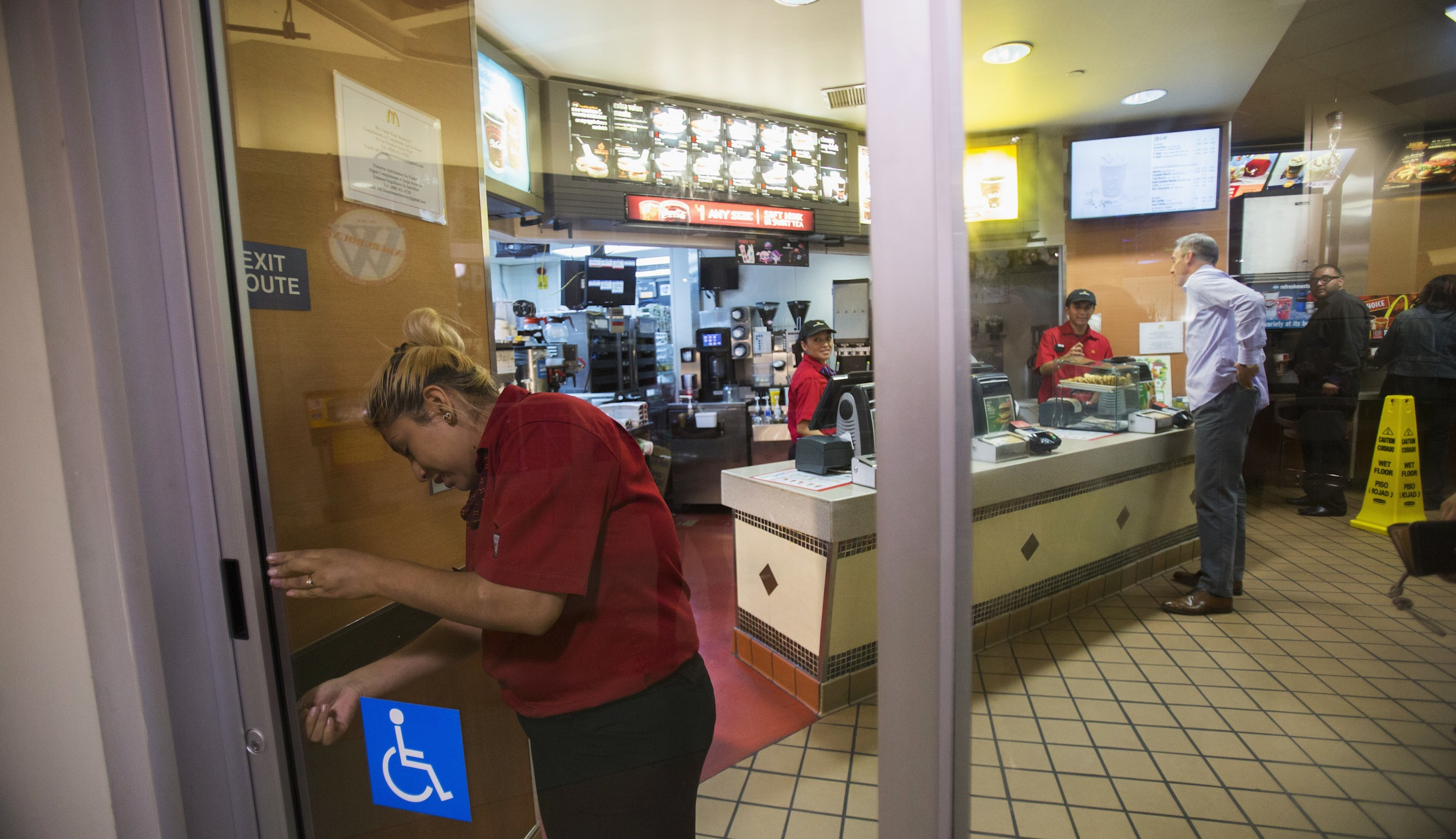 An employee locks the door of a McDonald's restaurant during a protest demanding better wages for fast-food workers, in Los Angeles, California September 4, 2014. U.S. fast-food workers staged protests in some 150 cities on Thursday in a fight for higher pay, and organizers said more than 450 were arrested from Manhattan's Times Square to Los Angeles. About 400 protesters clogged Times Square during morning rush hour in the latest of ongoing actions aimed at raising their wage to $15 an hour. In Los Angeles, protesters confronted managers inside two McDonald's restaurants.  REUTERS/Mario Anzuoni  (UNITED STATES - Tags: BUSINESS FOOD CIVIL UNREST EMPLOYMENT) - RTR4506F