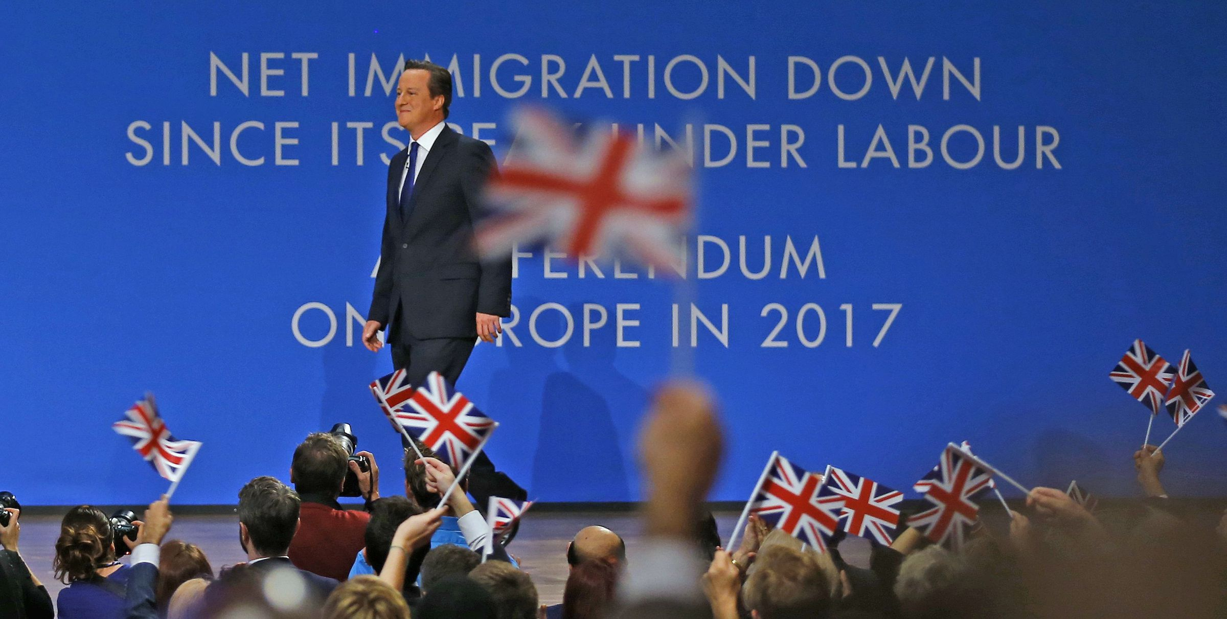Delegates wave flags as Britain's Prime Minister David Cameron takes to the stage to deliver his keynote address to the Conservative Party Conference in Birmingham, central England October 1, 2014.          REUTERS/Darren Staples (BRITAIN  - Tags: POLITICS)   - RTR48H4K