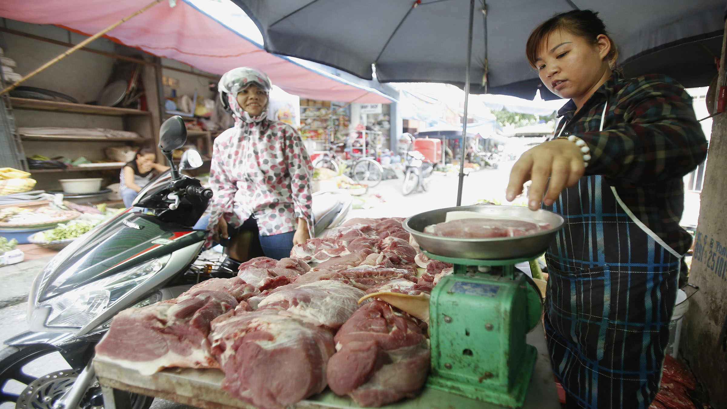 A meat vendor (R) weighs pork for sale at a roadside market in Hanoi October 2, 2014. Vietnam's annual inflation rate this year is forecast to be 3 percent to 4 percent, below a government target, as core inflation has been slowing in the past year, a government agency said in a report. REUTERS/Kham (VIETNAM - Tags: FOOD BUSINESS) - RTR48MM6