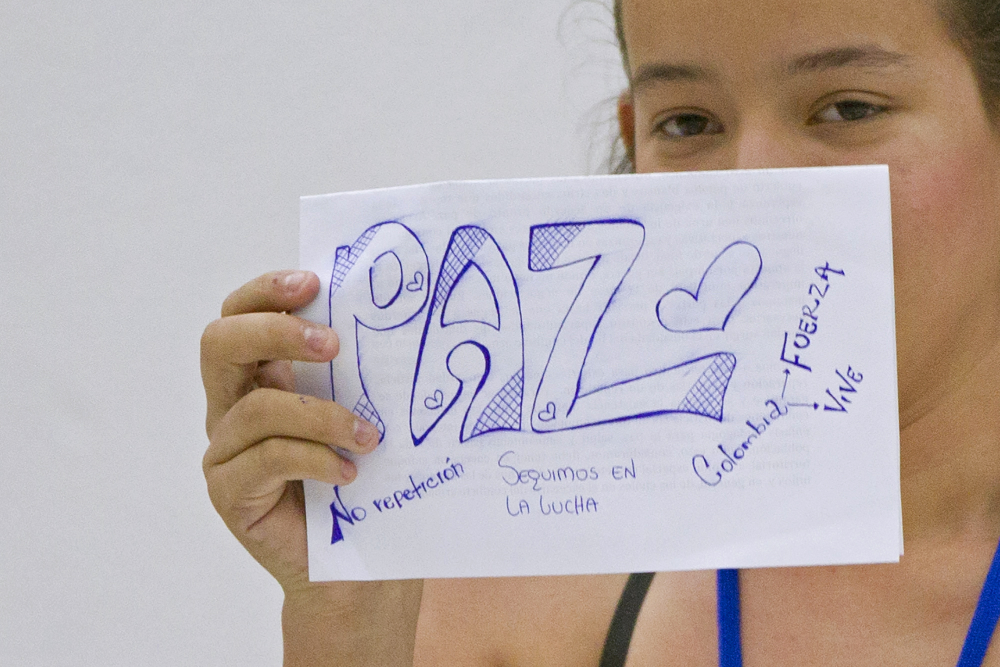 """Erika Paola Jaimes, a victim of the Colombian armed conflict, holds a paper that says """"Peace"""" during a conference for peace talks between the Revolutionary Armed Forces of Colombia (FARC) and the Colombian government in Havana October 2, 2014. The talks, an effort to end 50 years of war that has killed over 200,000 and displaced millions, are opposed by some political leaders, most notably hard-line ex-President and now senator Alvaro Uribe, who says they may lead to impunity for rebel leadership.   REUTERS/Alexandre Meneghini (CUBA - Tags: POLITICS CONFLICT) - RTR48R0U"""