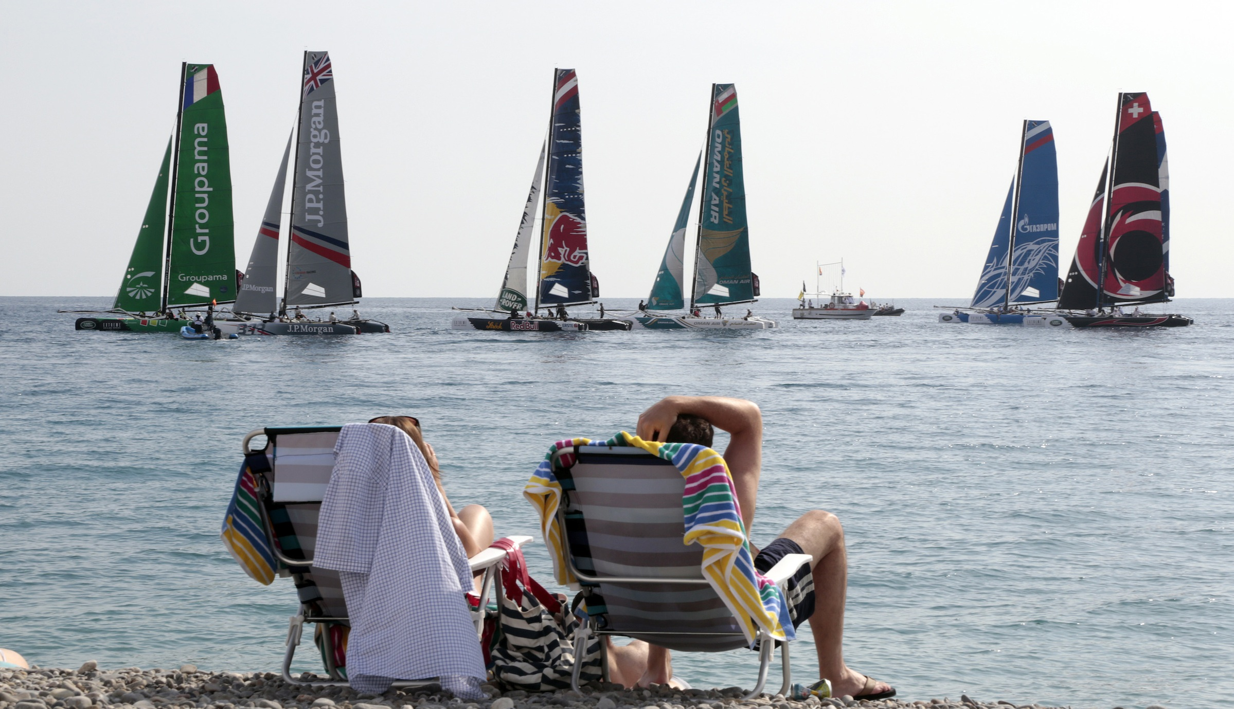 "People on the beach take advantage of warm weather to sit and watch the ""Extreme Sailing Series"" regatta on the Promenade Des Anglais in Nice, October 5, 2014.     REUTERS/Eric Gaillard (FRANCE - Tags: SPORT YACHTING SOCIETY ENVIRONMENT) - RTR4904P"