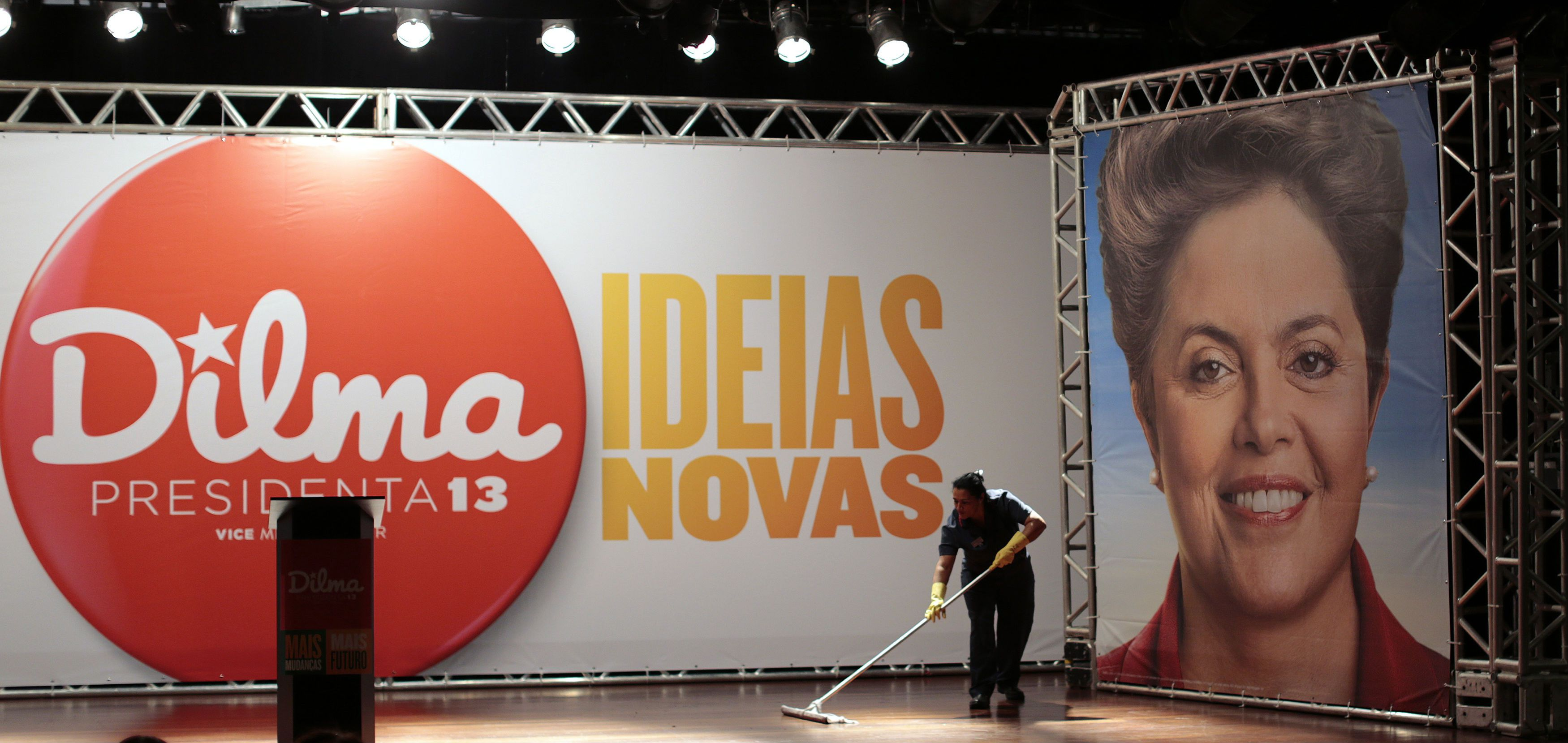"""A worker cleans the stage before the news conference of Brazil's President and Workers' Party (PT) candidate for re-election Dilma Rousseff in Brasilia, October 5, 2014. Brazilians voted in the first round of general elections on Sunday. The banner reads """"New Ideas"""". REUTERS/Ueslei Marcelino (BRAZIL - Tags: POLITICS ELECTIONS)"""