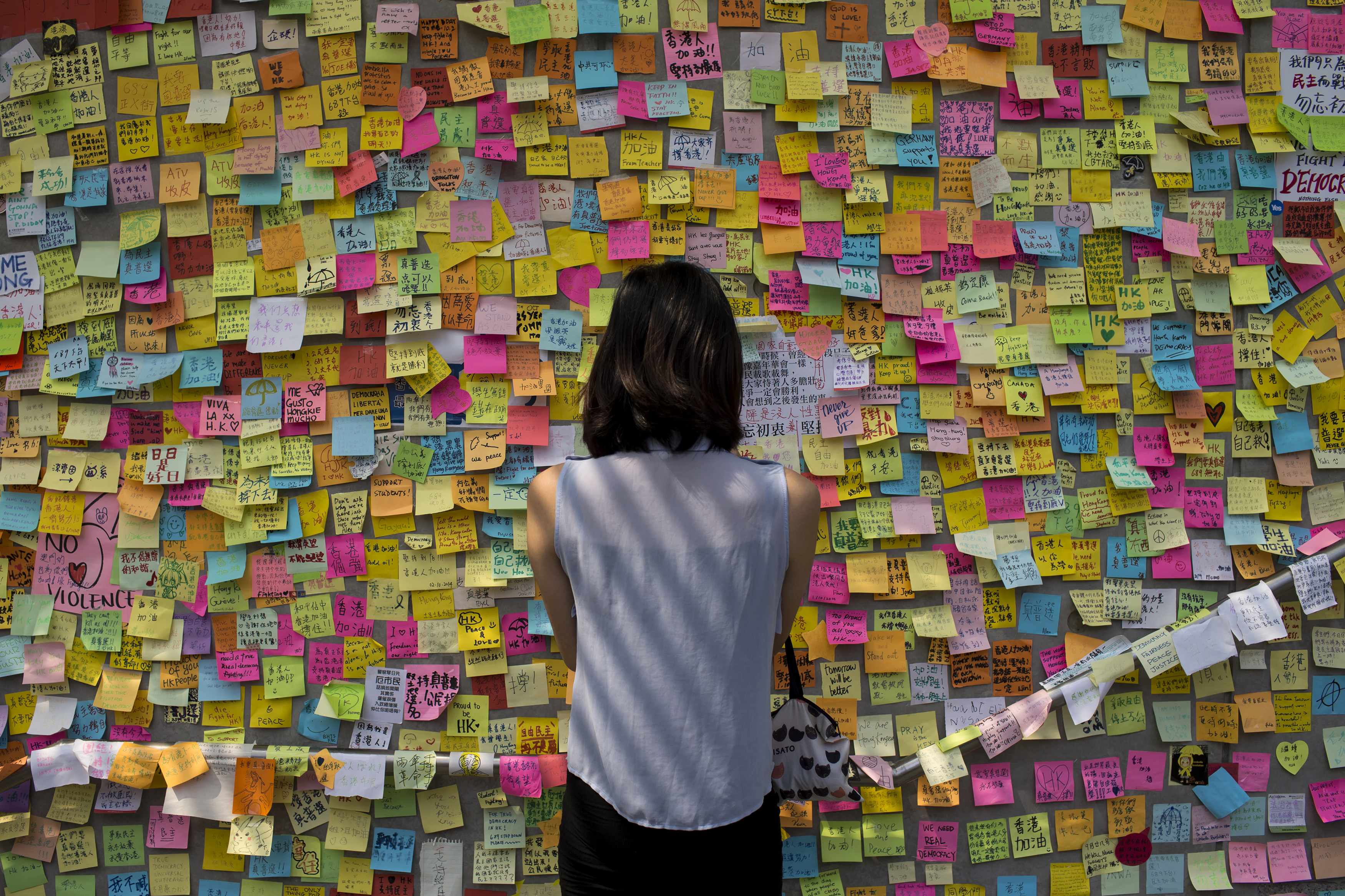 A woman looks at messages of support for pro-democracy demonstrations on a wall, as protesters block areas around government headquarters in Hong Kong October 7,2014. Pro-democracy demonstrations in Hong Kong rolled into early Tuesday with hundreds of students remaining camped out in the heart of the city after more than a week of rallies and behind-the-scenes talks showing modest signs of progress.   REUTERS/Tyrone Siu (CHINA - Tags: POLITICS CIVIL UNREST CRIME LAW) - RTR497KG