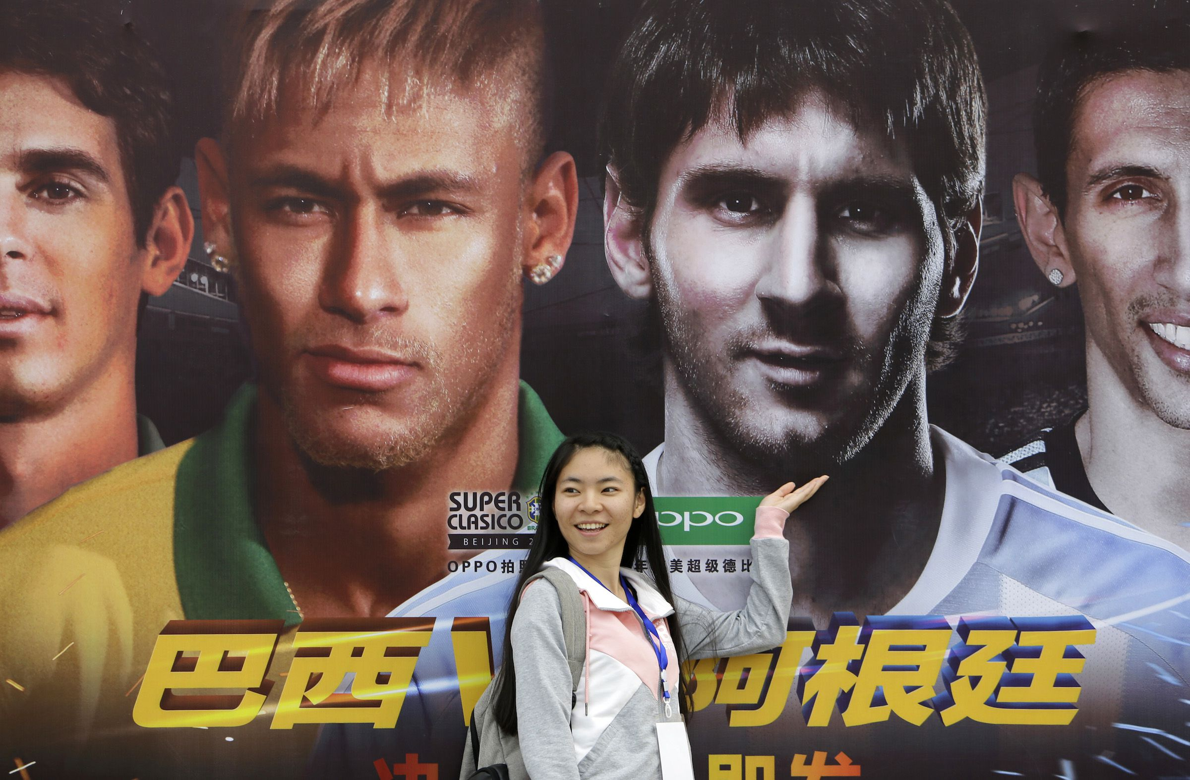 "A woman poses for photographs in front of a poster featuring Brazilian and Argentine soccer players (from L to R) Oscar, Neymar, Lionel Messi and Angel Di Maria, ahead of their international friendly soccer match titled ""the Super Classic of the Americas"", outside the National Stadium, or the Bird's Nest, in Beijing October 10, 2014. Brazil and Argentina will play their international friendly match in Beijing on Saturday. REUTERS/Jason Lee (CHINA - Tags: SPORT SOCCER) - RTR49N66"