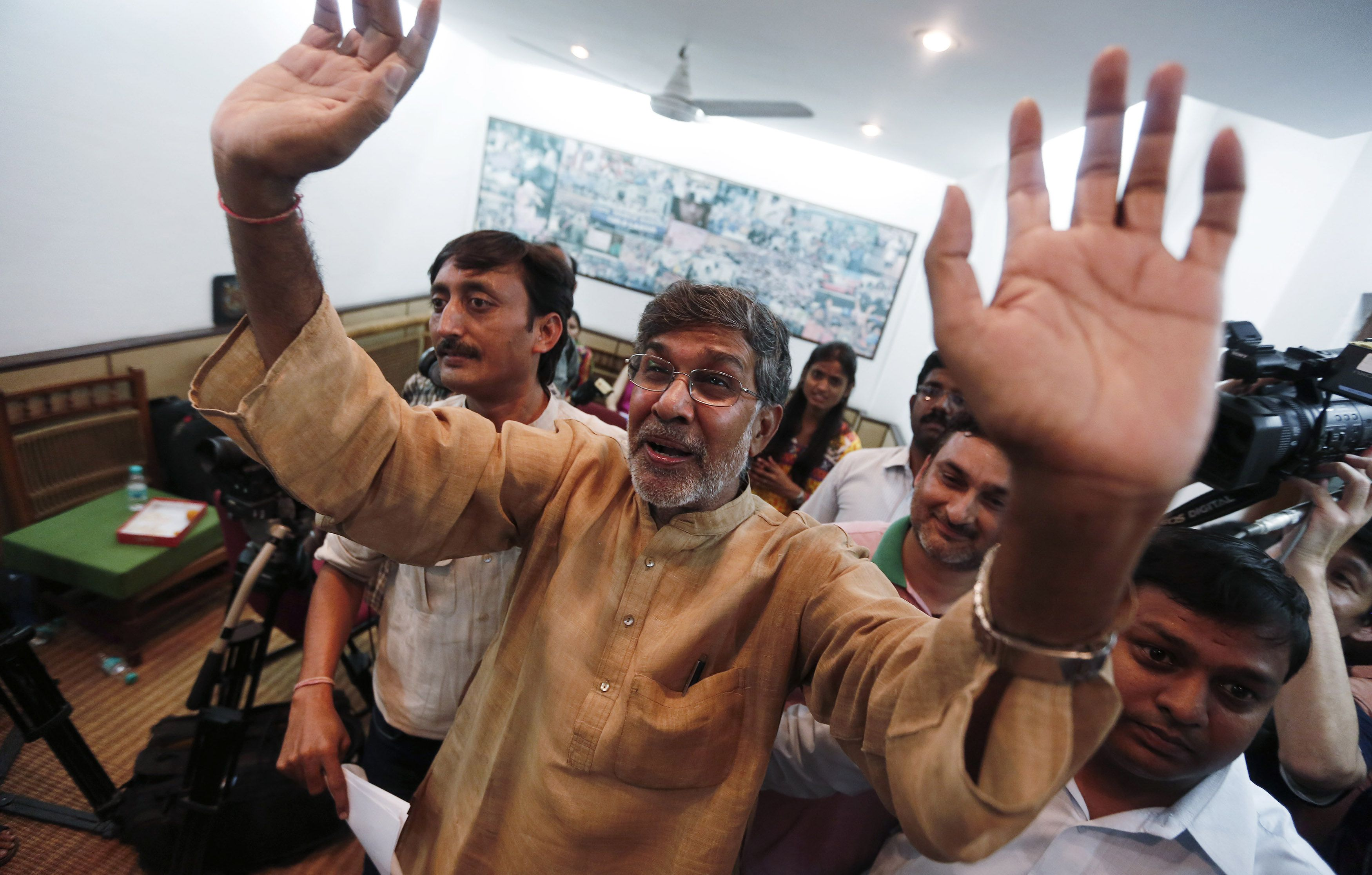 """Indian children's right activist Kailash Satyarthi waves to the media at his office in New Delhi October 10, 2014. Pakistani teenager Malala Yousafzai, who was shot in the head by the Taliban in 2012 for advocating girls' right to education, and Satyarthi won the 2014 Nobel Peace Prize on Friday. Satyarthi, 60, and Yousafzai were picked for their struggle against the oppression of children and young people, and for the right of all children to education, the Norwegian Nobel Committee said. Satyarthi dedicated the Nobel Peace Prize that he shared on Friday to children in slavery, pledging to """"join hands"""" with fellow laureate Yousafzai of Pakistan as their two countries fought over the territory of Kashmir. REUTERS/Adnan Abidi (INDIA - Tags: SOCIETY TPX IMAGES OF THE DAY) - RTR49P2B"""