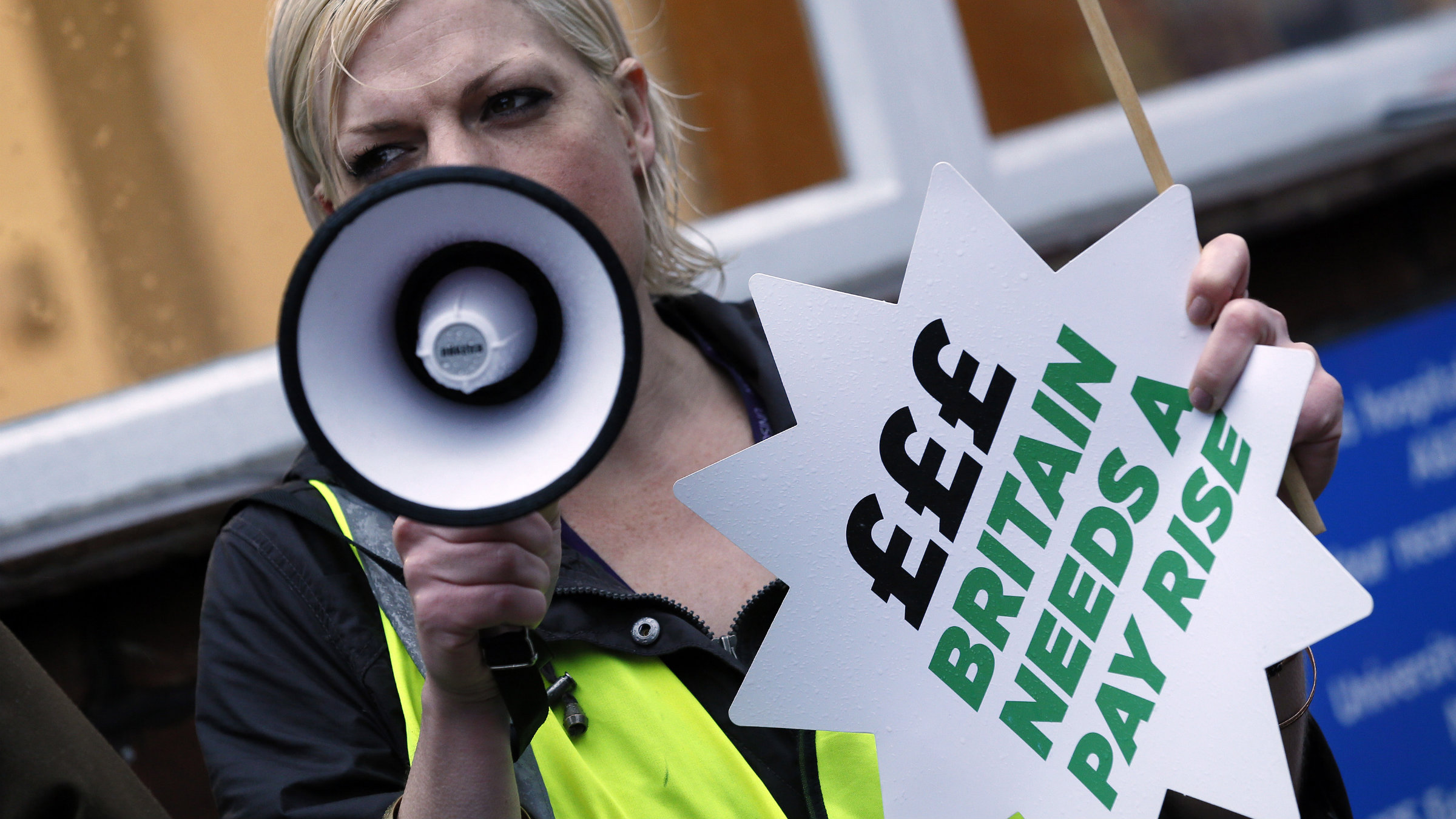 An NHS worker holds a placard and shouts through a megaphone during a strike, outside St Pancras Hospital in London October 13, 2014.