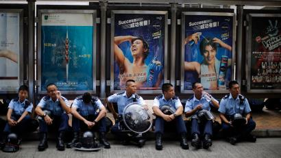 Policemen take a rest after removing barricades from a protest site in Admiralty near the government headquarters in Hong Kong October 14, 2014. Hong Kong police began a second day on Tuesday of removing some barricades erected by pro-democracy protesters in the bustling shopping district of Causeway Bay. Police removed some barricades early on Tuesday, according to a Reuters witness. Demonstrators have occupied the streets of the Chinese-controlled city for two weeks to demand greater democracy. REUTERS/Carlos Barria (CHINA - Tags: POLITICS CIVIL UNREST) - RTR4A2I1