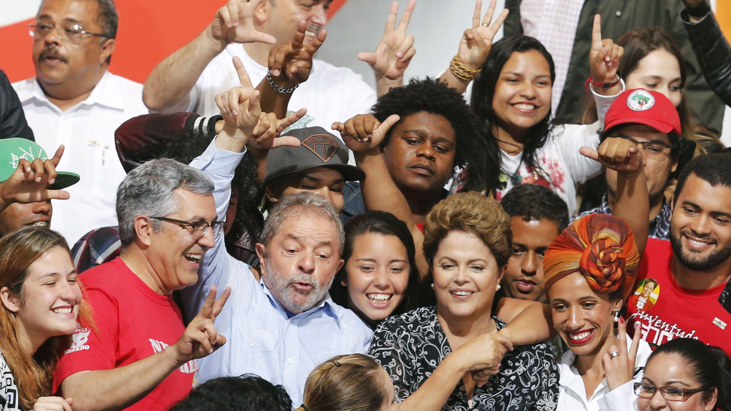 Brazil's President and Workers' Party (PT) presidential candidate Dilma Rousseff (front 3rd R) and Brazil's former President Luiz Inacio Lula da Silva (front 3rd L) pose for picture with supporters during a campaign rally in Sao Paulo October 20, 2014. President Dilma Rousseff is gaining momentum but remains locked in a dead heat with challenger Aecio Neves ahead of Sunday's runoff to Brazil's presidential election, a survey by pollster MDA showed on Monday. REUTERS/Paulo Whitaker (BRAZIL - Tags: POLITICS ELECTIONS)