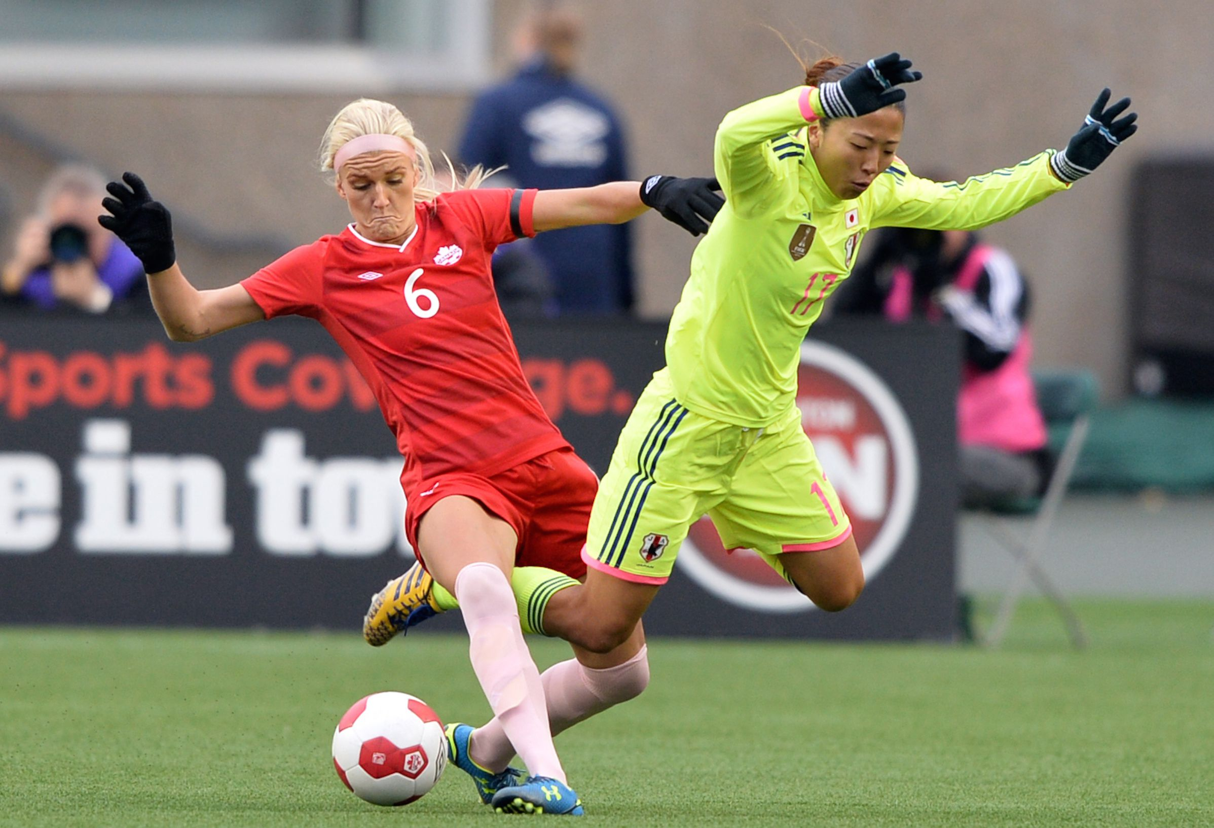 Oct 25, 2014; Edmonton, Alberta, Canada; Canada Kaylyn Kyle (6) knocks over Japan player Ogimi Yuki (17) in the first half at Commonwealth Stadium. Mandatory Credit: Chris LaFrance-USA TODAY Sports - RTR4BL6D