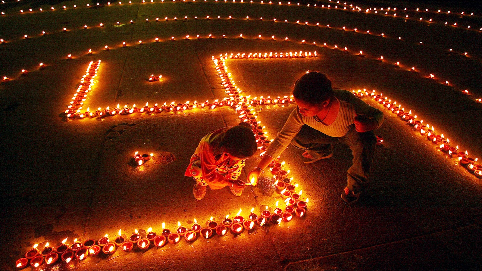 Children light lamps in the shape of Swastika, on the eve of Hindu festival of Diwali, in the northern city of Chandigarh, November 11, 2004. According to Hindu mythology, Swastika is the sign of prosperity. People decorate their homes with lights during the biggest Hindu festival of lights, Diwali that will be celebrated on November 12 this year.