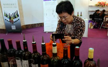 A woman takes pictures of labels of wine at Wine China Expo 2013 in Beijing September 24, 2013. China is the world's fifth-largest wine consumer, according to a study last year for VINEXPO, an annual wine trade show that alternates between Bordeaux and Hong Kong. The study forecast annual consumption growth in China and Hong Kong at 54.3 percent between 2011 and 2015, or a billion more bottles every year. REUTERS/Kim Kyung-Hoon (CHINA - Tags: FOOD BUSINESS SOCIETY) - RTX13XE3