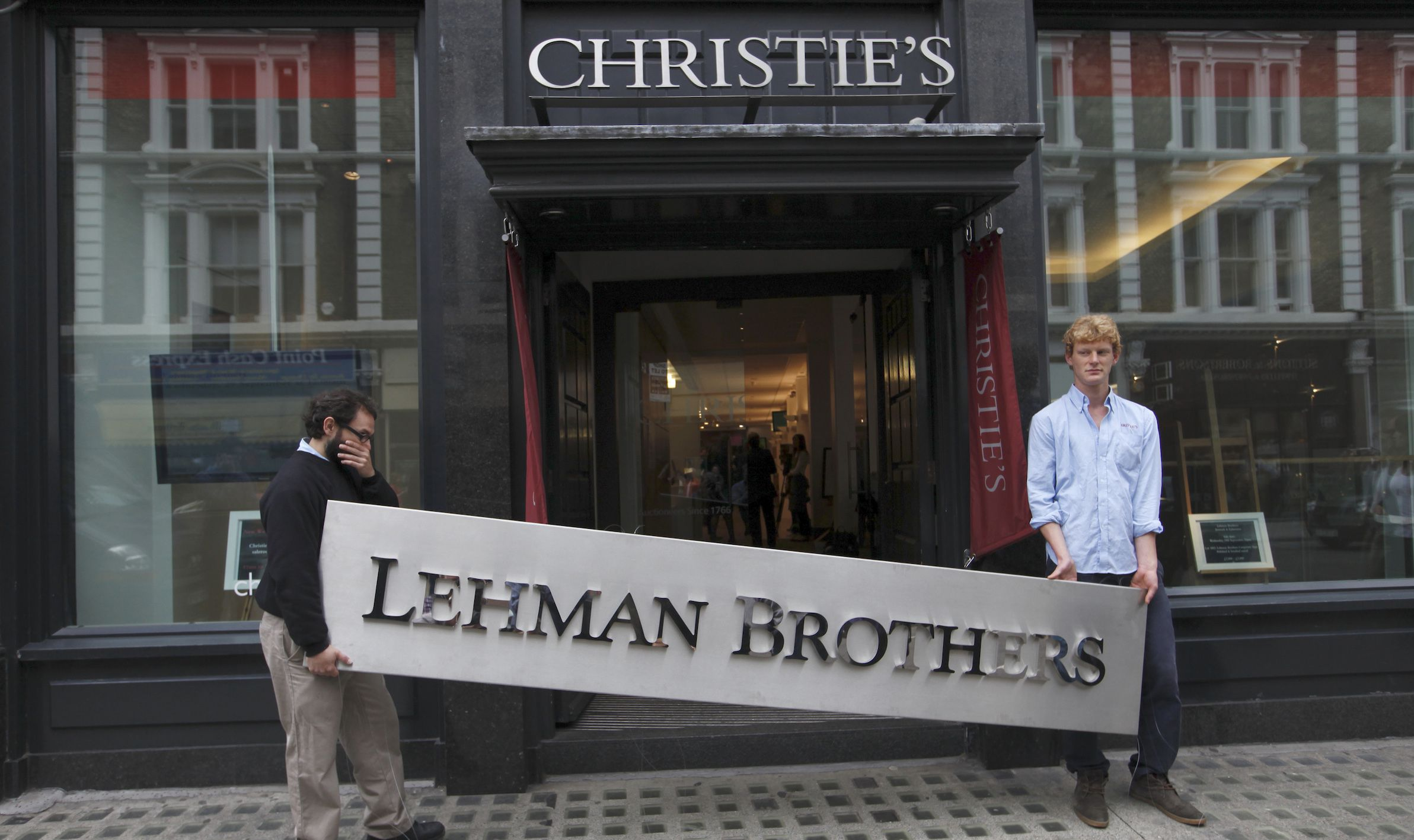 Christie's employees pose for a photograph with a Lehman Brothers sign at Christie's in central London September 24, 2010. Various items are on display before the auction of Lehman Brothers: Artwork and Ephemera, which will take place on September 29. REUTERS/Andrew Winning (BRITAIN - Tags: ENTERTAINMENT BUSINESS SOCIETY) - RTXSLK5