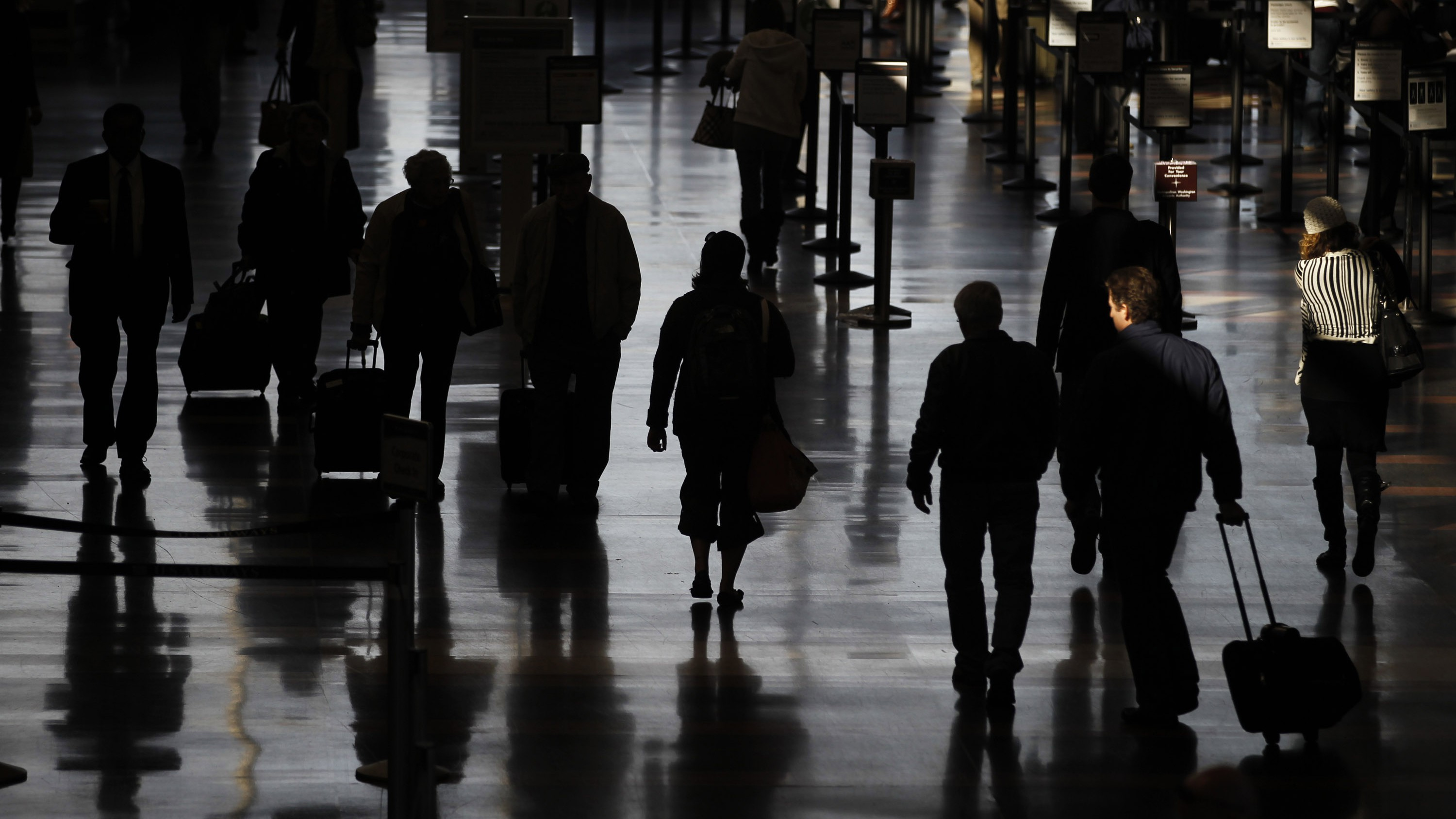 Travellers walk to their flights at the Ronald Reagan Washington National Airport in Washington November 24, 2010. Millions of Americans took to the skies on Wednesday for the start of the Thanksgiving holiday amid protests by some travellers about heightened, more invasive security procedures.