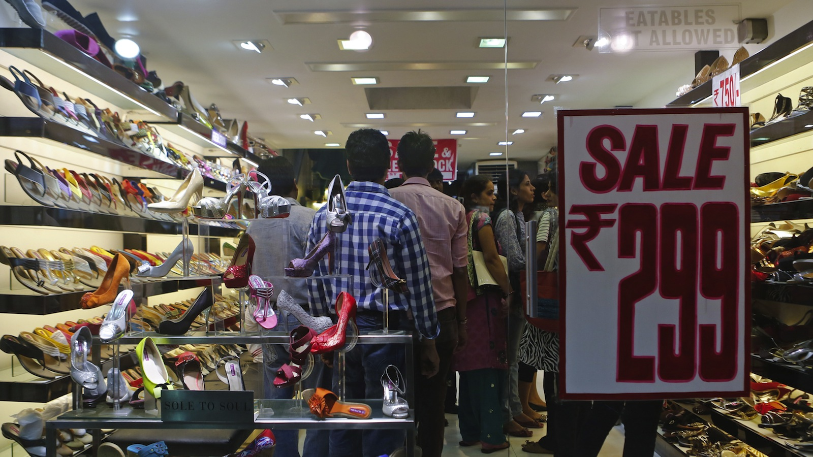 People shop inside a shoe store on a street in Mumbai September 11, 2013. In a capitulation that speaks to the depth of the slump in India's economy, usually tight-fisted retail landlords have become uncharacteristically flexible on rents. Retailers in India say they can now negotiate revenue sharing deals or discounts on rent of up to 20 percent and many are jumping at the chance, not necessarily because they see a bottom to the economic downturn but because the supply of new retail space is expected to tighten sharply from 2015. Picture taken September 11, 2013.