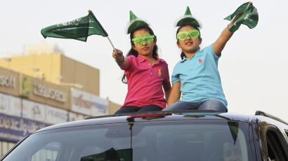 Girls wave Saudi Arabia's national flags as they ride a car, as the oil-rich Gulf Arab country celebrates its National Day, in Riyadh September 23, 2013.