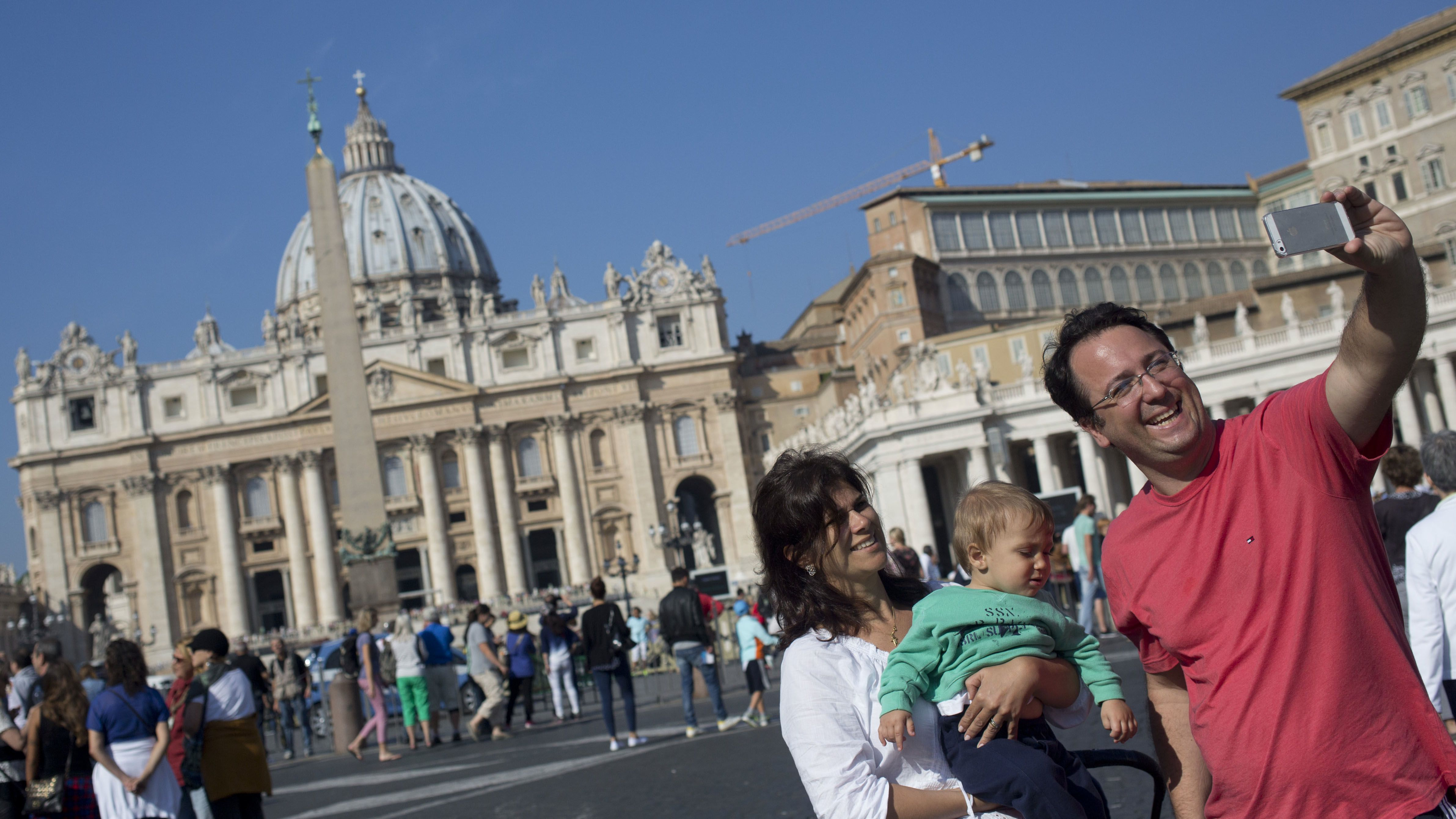"""A family take a """"selfie"""" in front of St. Peter's Basilica at the Vatican, Saturday, Oct. 4, 2014. Pope Francis on Sunday will open a two-week meeting of bishops and cardinals from around the world aimed at making the church's teaching on family life — marriage, sex, contraception, divorce and homosexuality — relevant to today's Catholic families and more readily understood and appreciated.  (AP Photo/Alessandra Tarantino)"""
