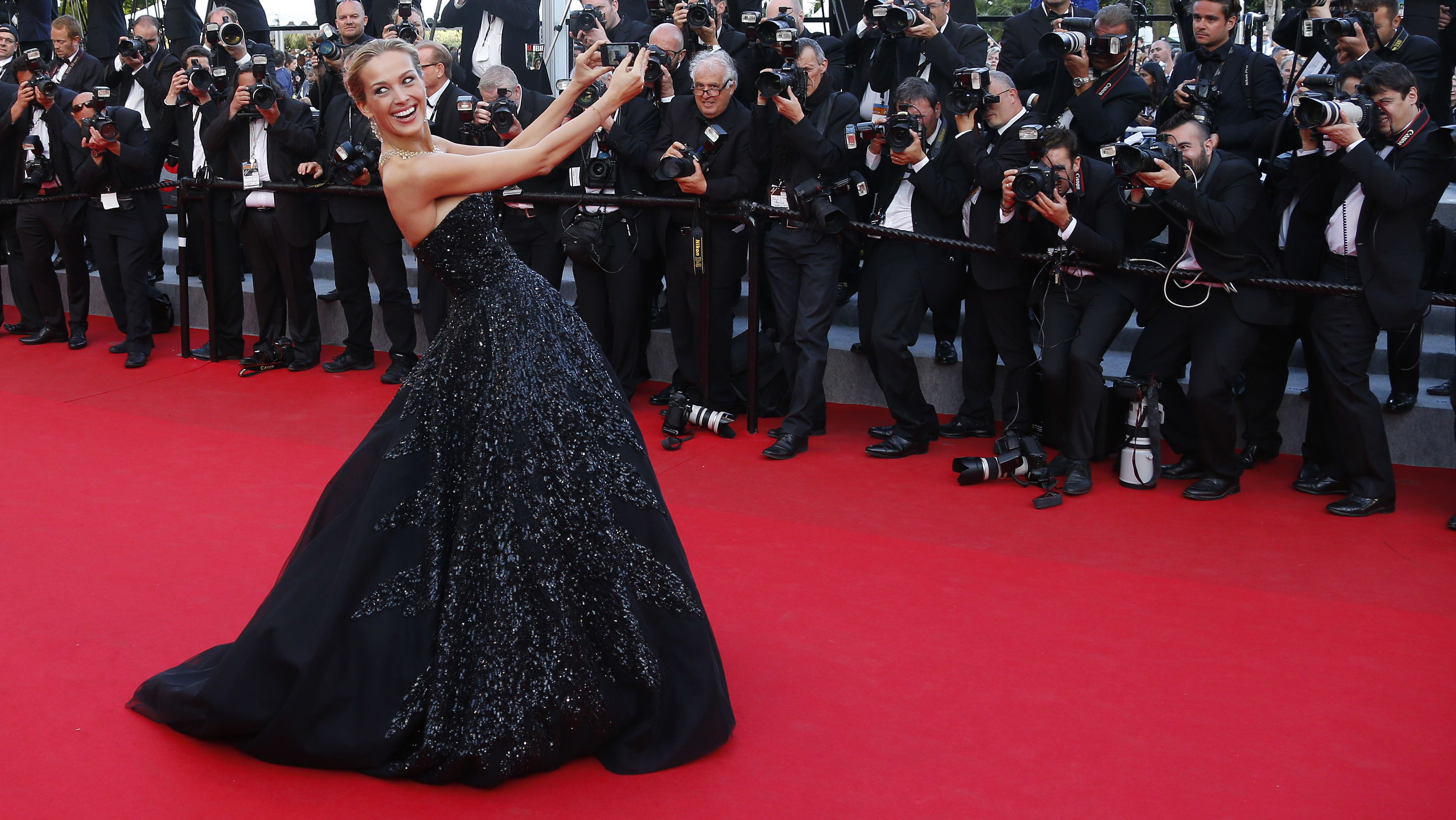 "Model Petra Nemcova takes a selfie with a mobile phone as she poses on the red carpet for the screening of the film ""Deux jours, une nuit"" (Two Days, One Night) in competition at the 67th Cannes Film Festival in Cannes May 20, 2014.          REUTERS/Yves Herman (FRANCE  - Tags: ENTERTAINMENT)   - RTR3Q29G"