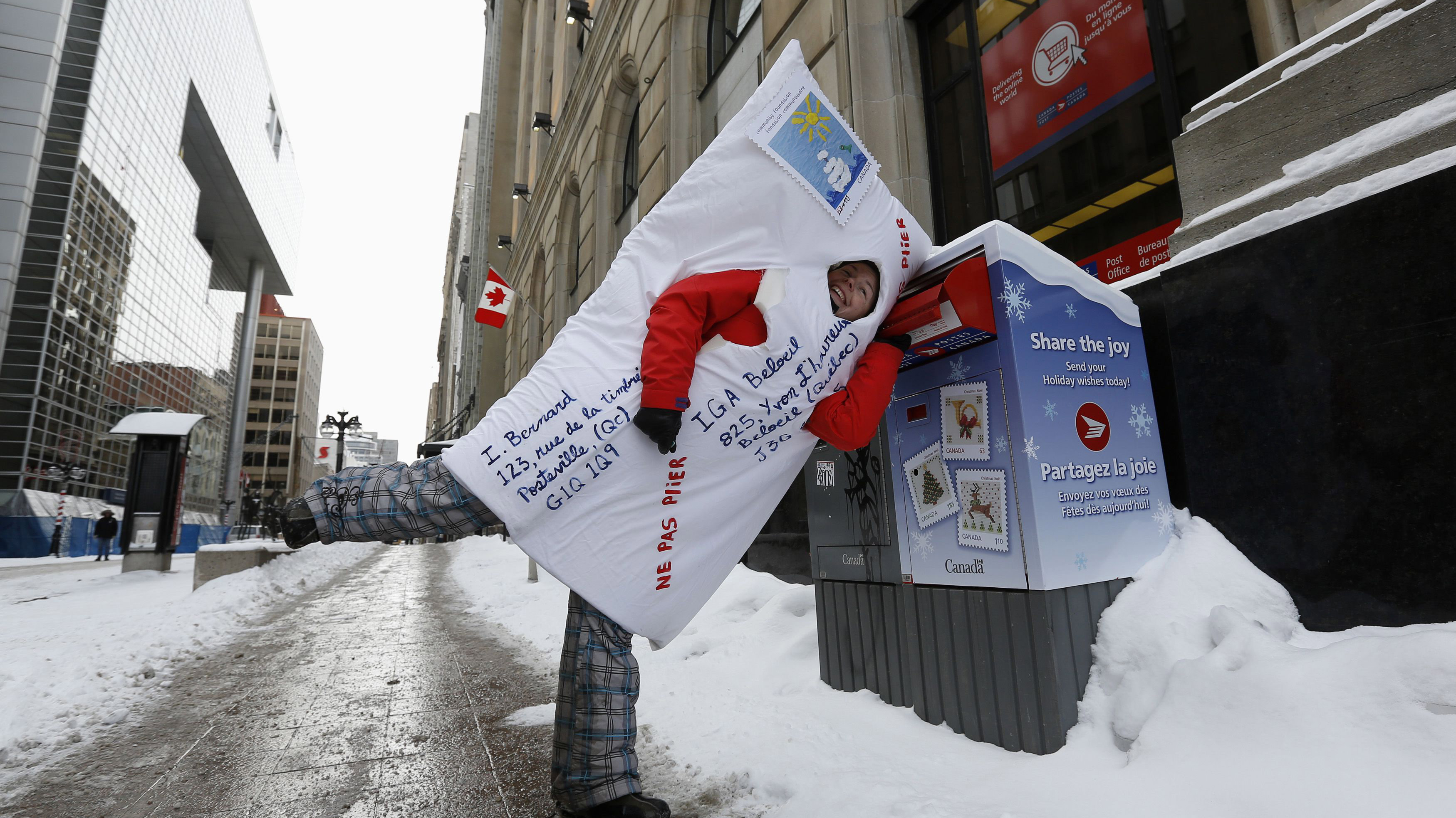 A demonstrator dressed as a mailed envelope jokes around with a mailbox during a protest against planned cuts to Canada Post in Ottawa January 26, 2014. Canada's postal service will phase out urban home delivery within five years and hike the cost of postage stamps to try to stem soaring losses, the post office announced last month. REUTERS/Chris Wattie