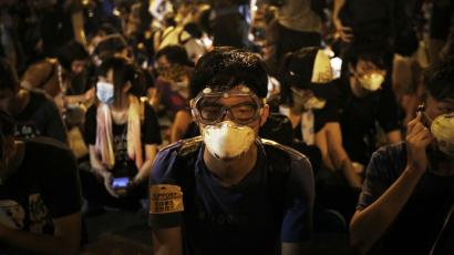 Student protesters sit on the main road outside the government complex where Hong Kong's Chief Executive Leung Chun-ying's office is located, Friday, Oct. 3, 2014 in Hong Kong.