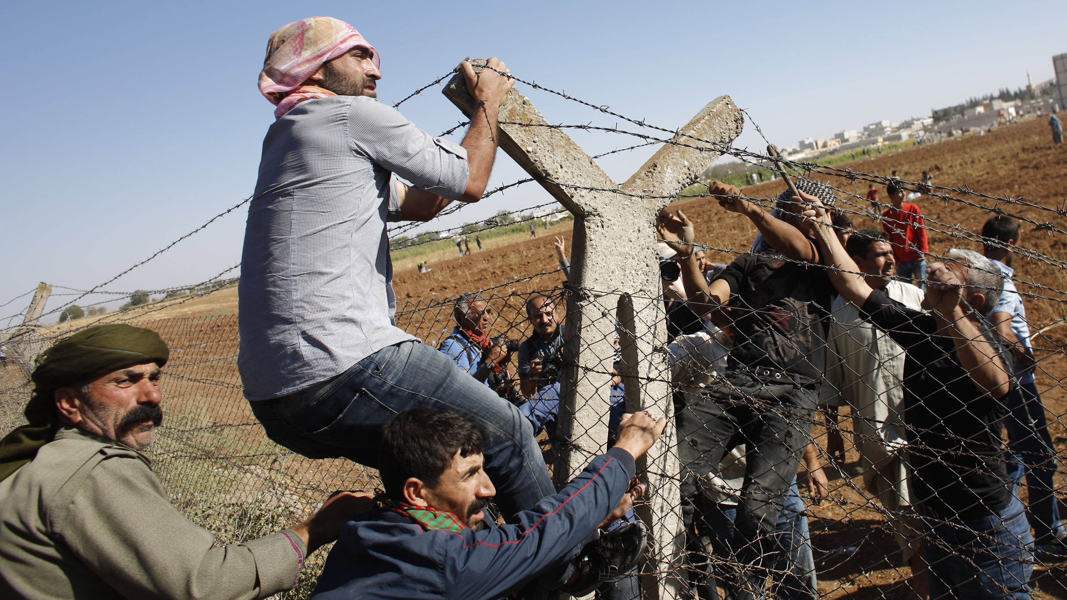 DATE IMPORTED:September 26, 2014Turkish and Syrian Kurds pull down a part of the Turkish-Syrian border fence, near the southeastern town of Suruc in Sanliurfa province September 26, 2014. Islamic State fighters tightened their siege of the strategic town of Kobani on Syria's border with Turkey on Friday, pushing back Kurdish forces and sending shells into Turkish territory, witnesses said. Several hundred unarmed protesters who had gathered on the Turkish side of the border in solidarity with the Syrian Kurds at one point broke through a barbed wire fence and rushed towards Kobani in an apparent bid to help defend it. The group, including pro-Kurdish politicians from Turkey, later gathered on a railway line on the Syrian side of the border, clashing with Turkish security forces who fired tear gas and were initially reluctant to let them back in.