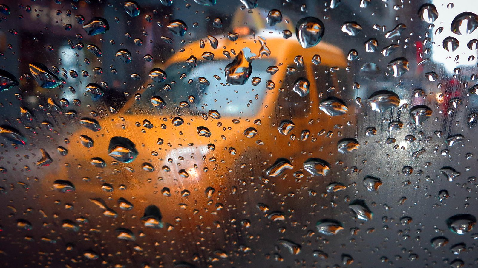 A taxi is pictured through the window of another taxi in the rain in Times Square in New York February 5, 2014. The latest in a series of winter storms hit the United States on Wednesday, threatening to drop up to a foot of snow in central New England, snarling travel and eating into supplies of salt needed to keep roads clear.