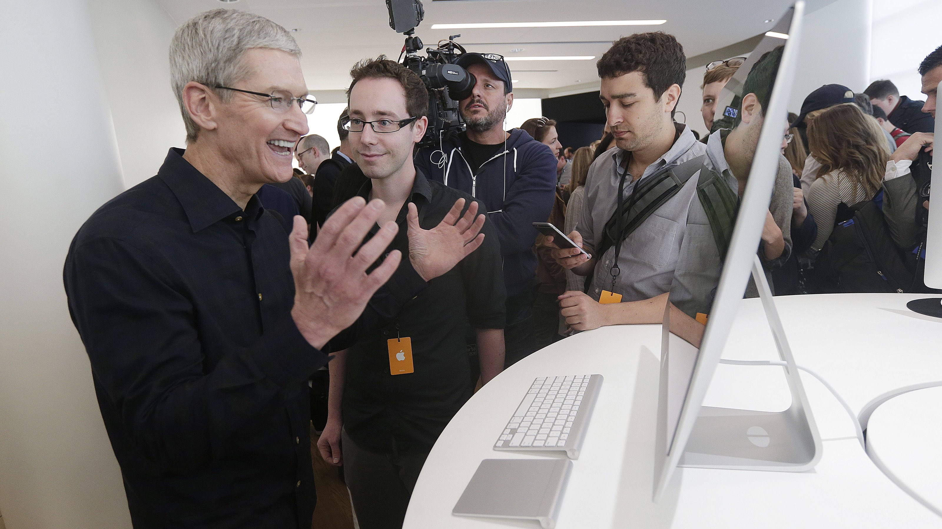 Apple CEO Tim Cook jokes with an employee as he looks at a new iMac at Apple headquarters on Thursday, Oct. 16, 2014 in Cupertino, Calif. Apple released an update to its Mac operating system and introduced the high-resolution iMac model that might appeal to heavy watchers of television over the Internet. (AP Photo/Marcio Jose Sanchez)