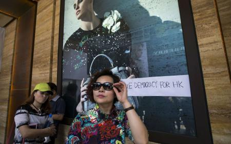 "Chinese tourists walk past a slogan reading ""True Democracy for HK"" outside a luxury shop along a main street at Hong Kong's shopping district Tsim Sha Tsui October 1, 2014.Thousands of pro-democracy protesters thronged the streets of Hong Kong on Wednesday, ratcheting up pressure on the pro-Beijing government that has called the action illegal, with both sides marking uneasy National Day celebrations."