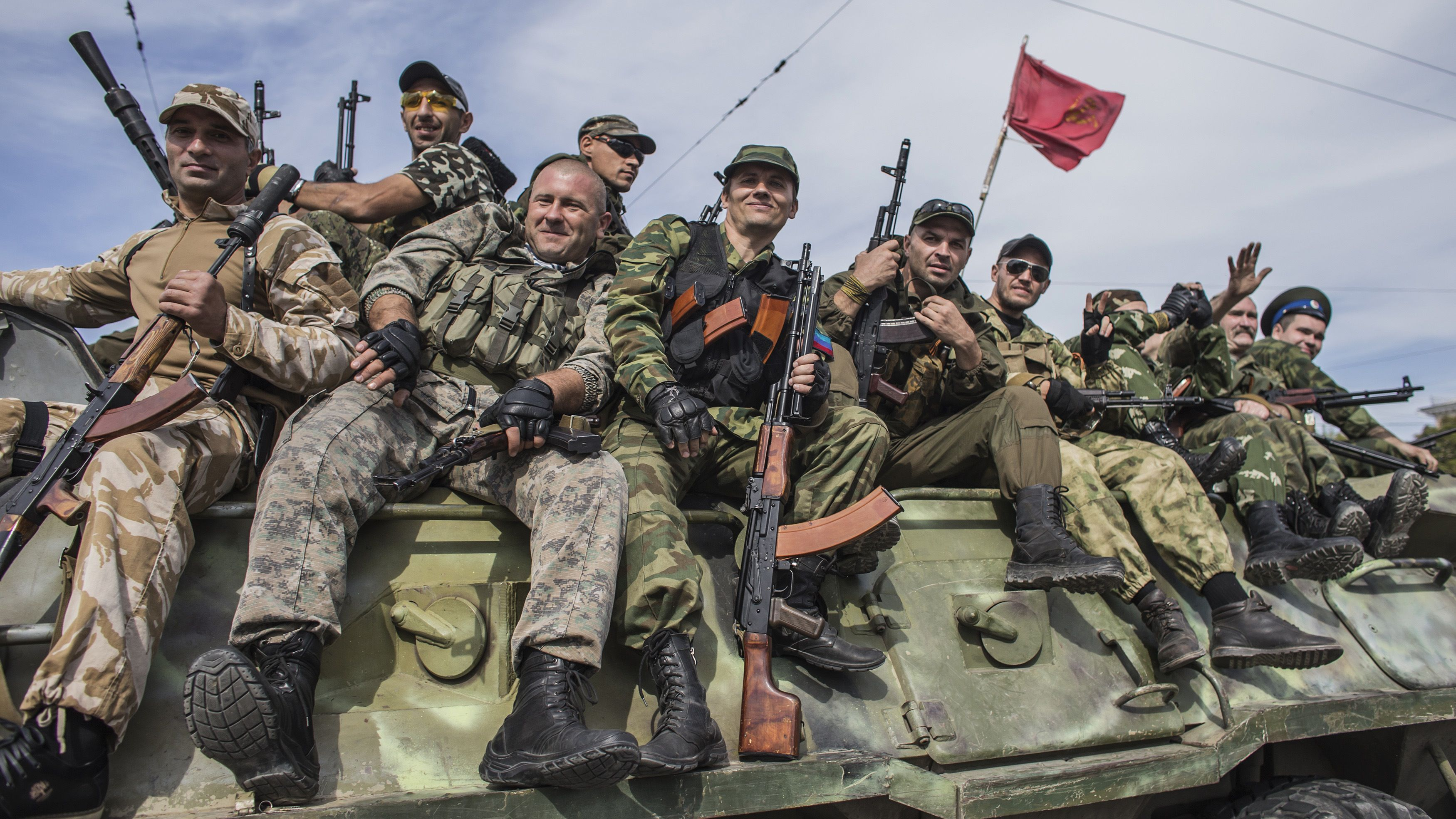"""Pro-Russian rebels ride on an armored personnel carrier (APC) during a parade in Luhansk, eastern Ukraine, September 14, 2014. Ukraine's Defence Minister said on Sunday that NATO countries were delivering weapons to his country to equip it to fight pro-Russian separatists and """"stop"""" Russian President Vladimir Putin. Valery Heletey told a news conference he had discussed weapons deliveries in bilateral meetings with NATO defence ministers during a NATO summit in Wales on Sept. 4-5. REUTERS/Marko Djurica (UKRAINE - Tags: POLITICS CIVIL UNREST MILITARY CONFLICT) - RTR466G7"""