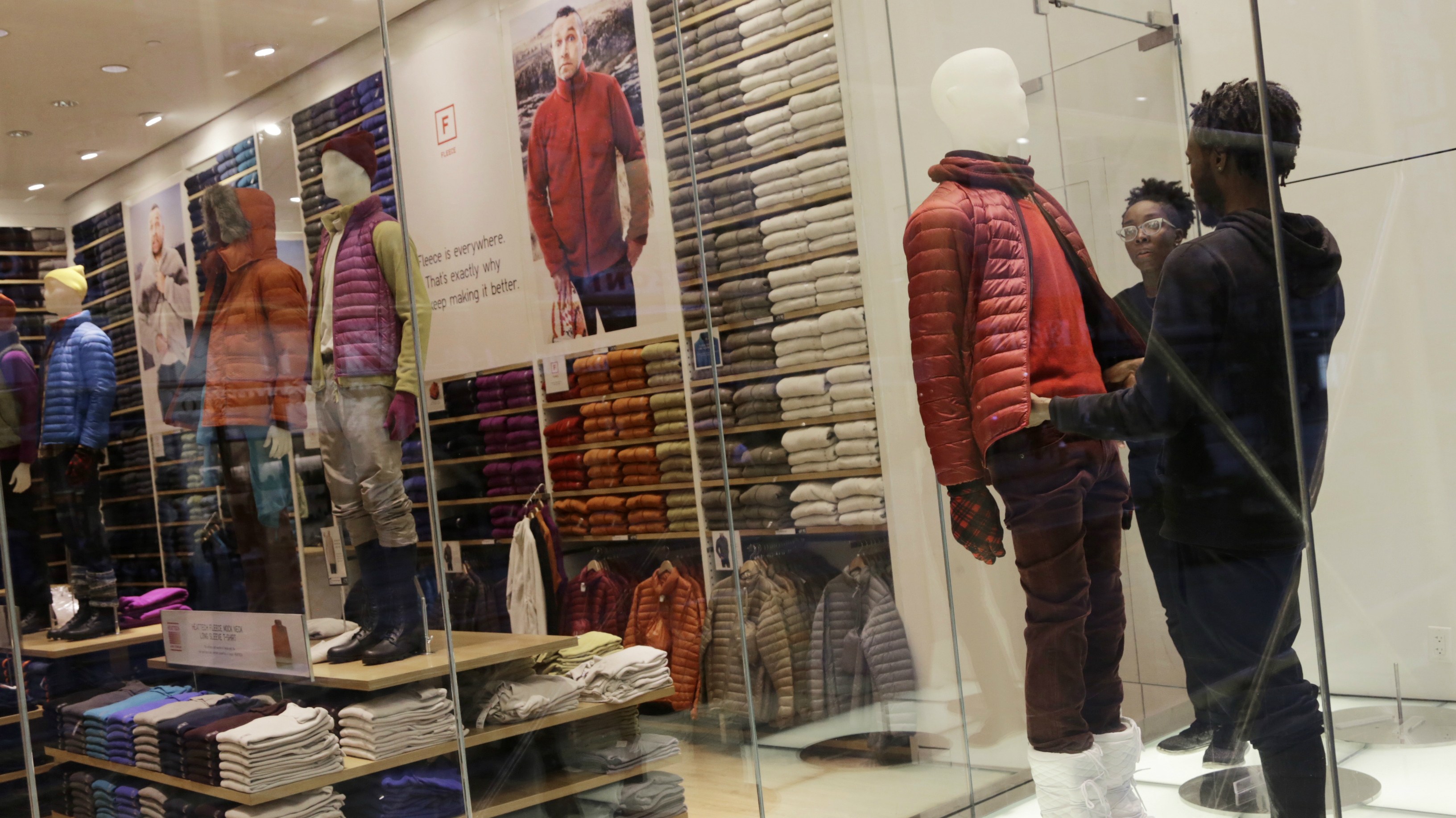 Store employees arrange a mannequin in a Uniqlo display window, Monday, Nov. 18, 2013 in New York. (AP Photo/Mark Lennihan)