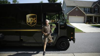 In this June 20, 2014 photo, United Parcel Service driver Marty Thompson steps off a truck while making a delivery in Cumming, Ga. UPS reports quarterly earnings on Tuesday, July 29, 2014. (AP Photo/David Goldman)