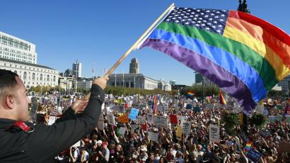 Alexander Sanchez of San Francisco, waves a rainbow colored flag to a large crowd of supporters of same-sex marriage as they cheer in front of San Francisco City Hall on Saturday, Nov. 15, 2008. Thousands of demonstrators gathered to listen to speakers and protest the passage of Proposition 8, a ballot measure amending California's constitution to ban same-sex marriage. The event is part of a simultaneous protest planned in hundreds of communities. (AP Photo/Darryl Bush)