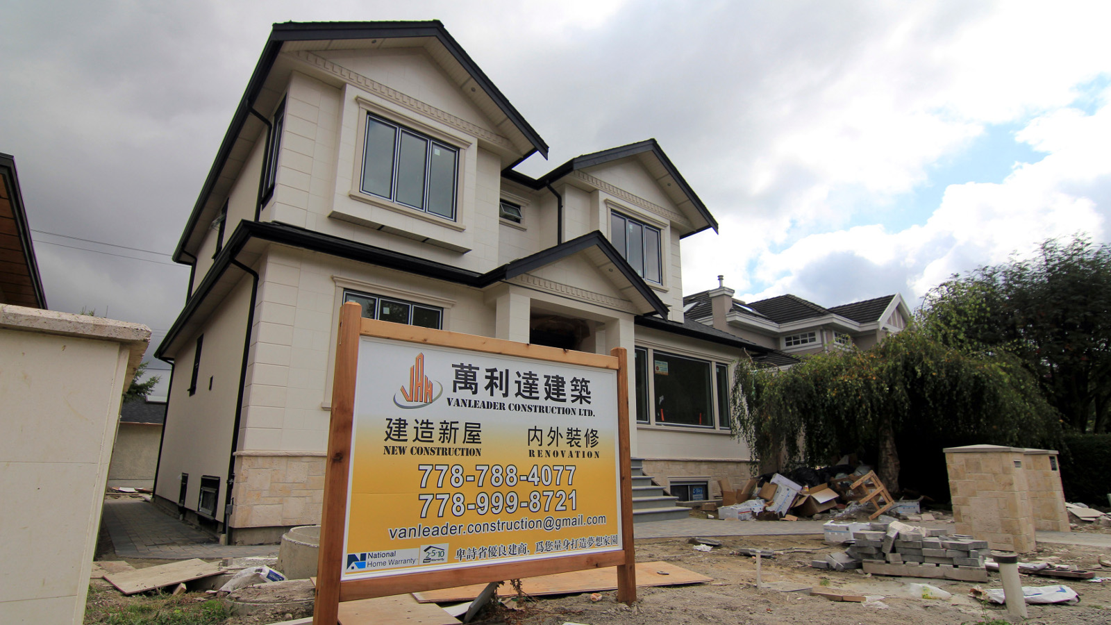 A contractor's sign stands outside a mansion currently under construction in a Vancouver neighbourhood popular with Chinese buyers September 9, 2014. Chinese investors' global hunt for prime real estate is helping drive Vancouver home prices to record highs and the city, long among top destinations for wealthy mainland buyers, is feeling the bonanza's unwelcome side-effects. The latest wave of Chinese money is flowing into luxury hot spots. But it has also started driving up housing costs elsewhere in a city which already ranks as North America's least affordable urban market. Picture taken September 9.
