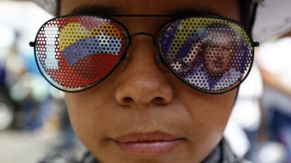 A supporter of Venezuela's President Nicolas Maduro wears a pair of sunglasses with a picture of late Venezuelan president Hugo Chavez, during a rally in support of Maduro in Caracas October 18, 2014. Both supporters and detractors of Venezuela's government marched through the capital Caracas on Saturday. Supporters of Maduro were protesting this month's killing of a young 'Chavista' lawmaker, a crime the government has blamed on political opponents, including Colombian paramilitary forces. Separately, the opposition demonstrated against a laundry list of issues, including a slumping economy, shortages of basic goods, and sky-high crime rates. REUTERS/Jorge Silva (VENEZUELA - Tags: POLITICS CIVIL UNREST TPX IMAGES OF THE DAY)