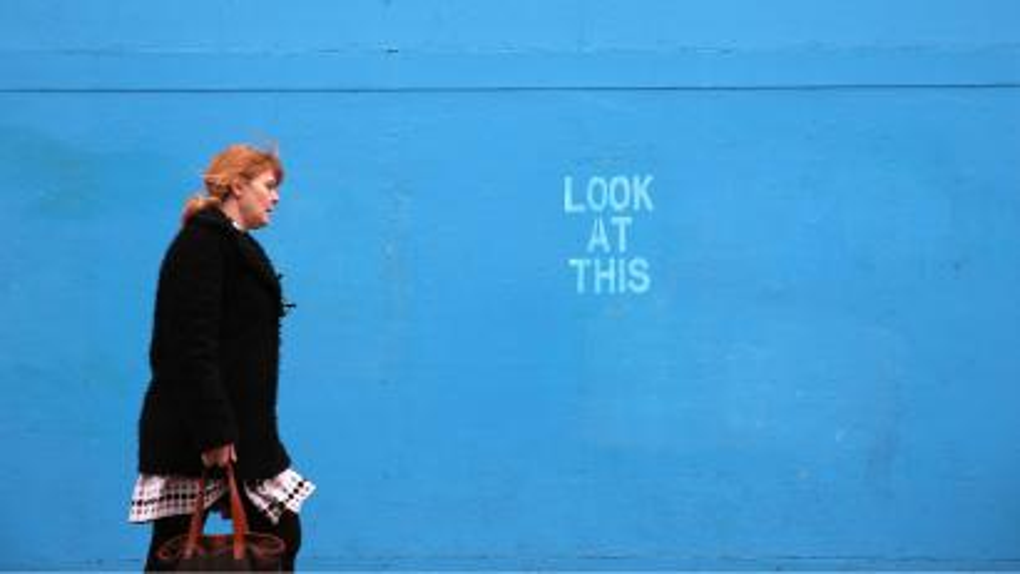 Woman walking past a blue wall