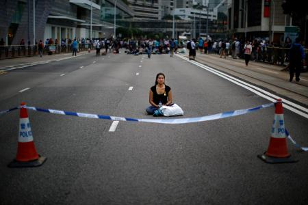 A woman meditates at a protest site after clashes between anti-occupy Central demonstrators and pro-democracy protesters near the government