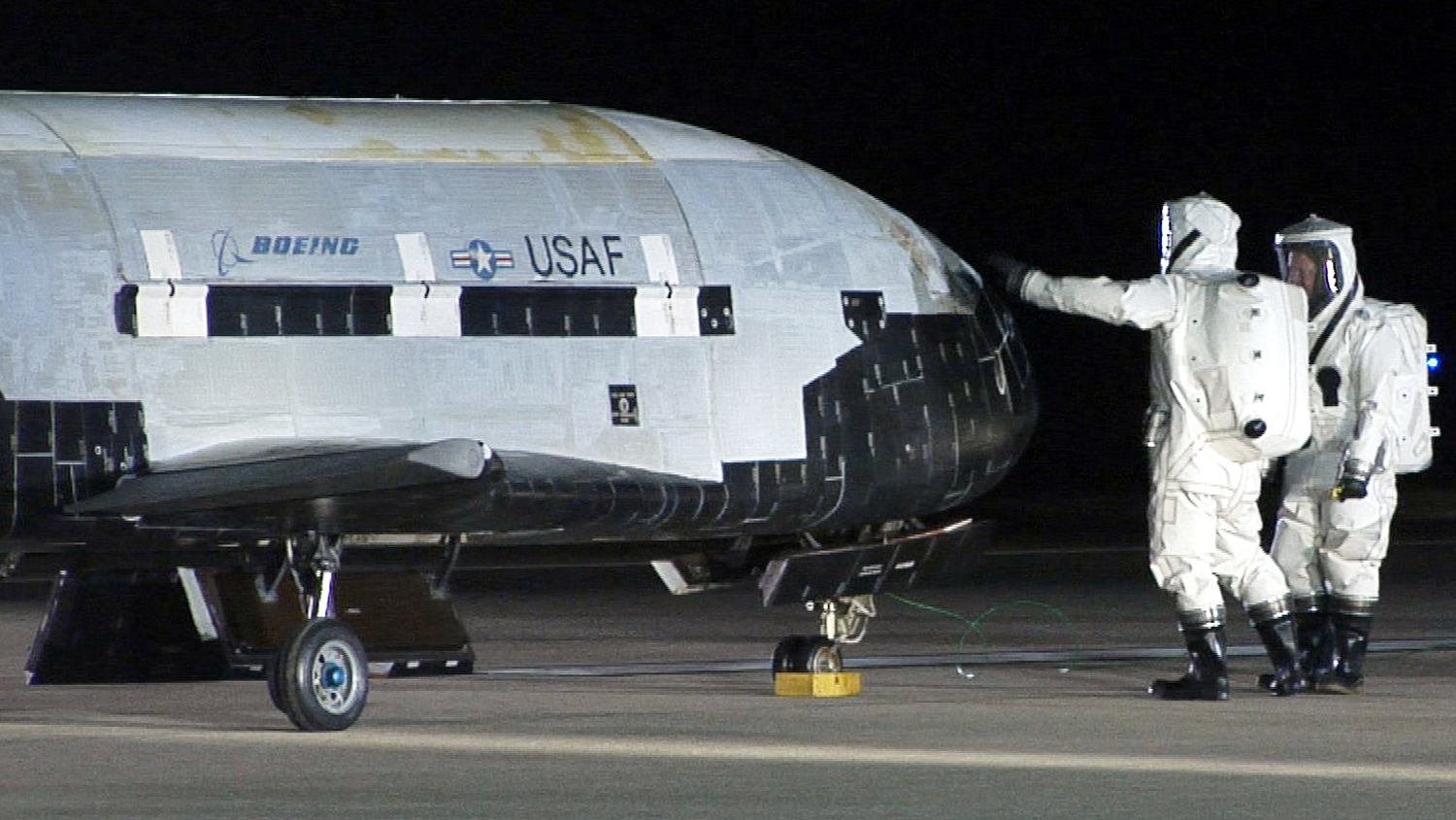 This image provided by Vandenberg Air Force Base shows technicians examining the X-37B unmanned spaceplane shortly after landing Friday Dec. 3, 2010 at Vandenberg Air Force Base, Calif. The X-37B slipped out of orbit and landed after a successful maiden flight that lasted more than seven months, the Air Force said.