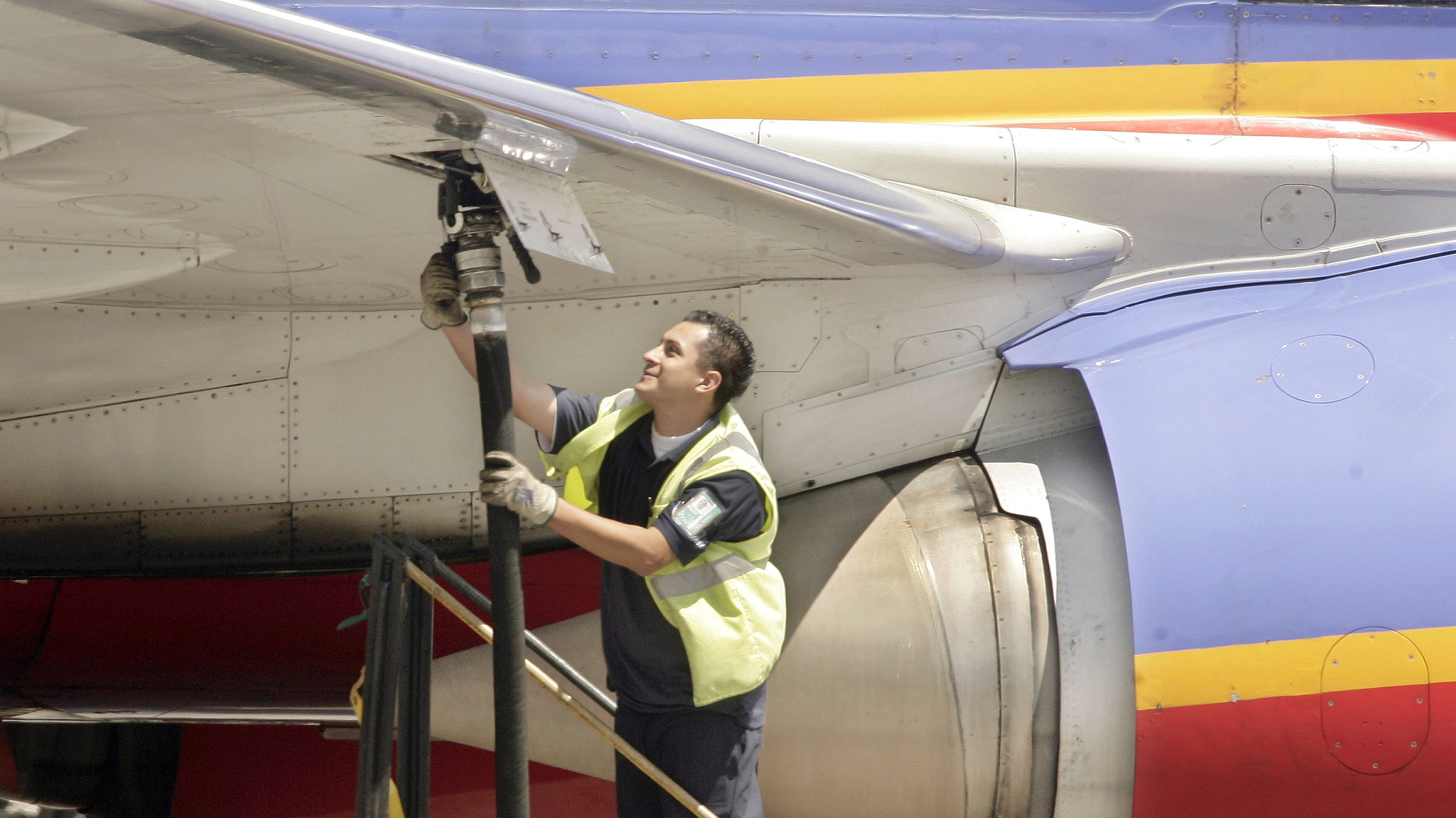 an aviation ground crew member pumps fuel into a Southwest Airlines' plane at Los Angeles International Airport in Los Angeles.