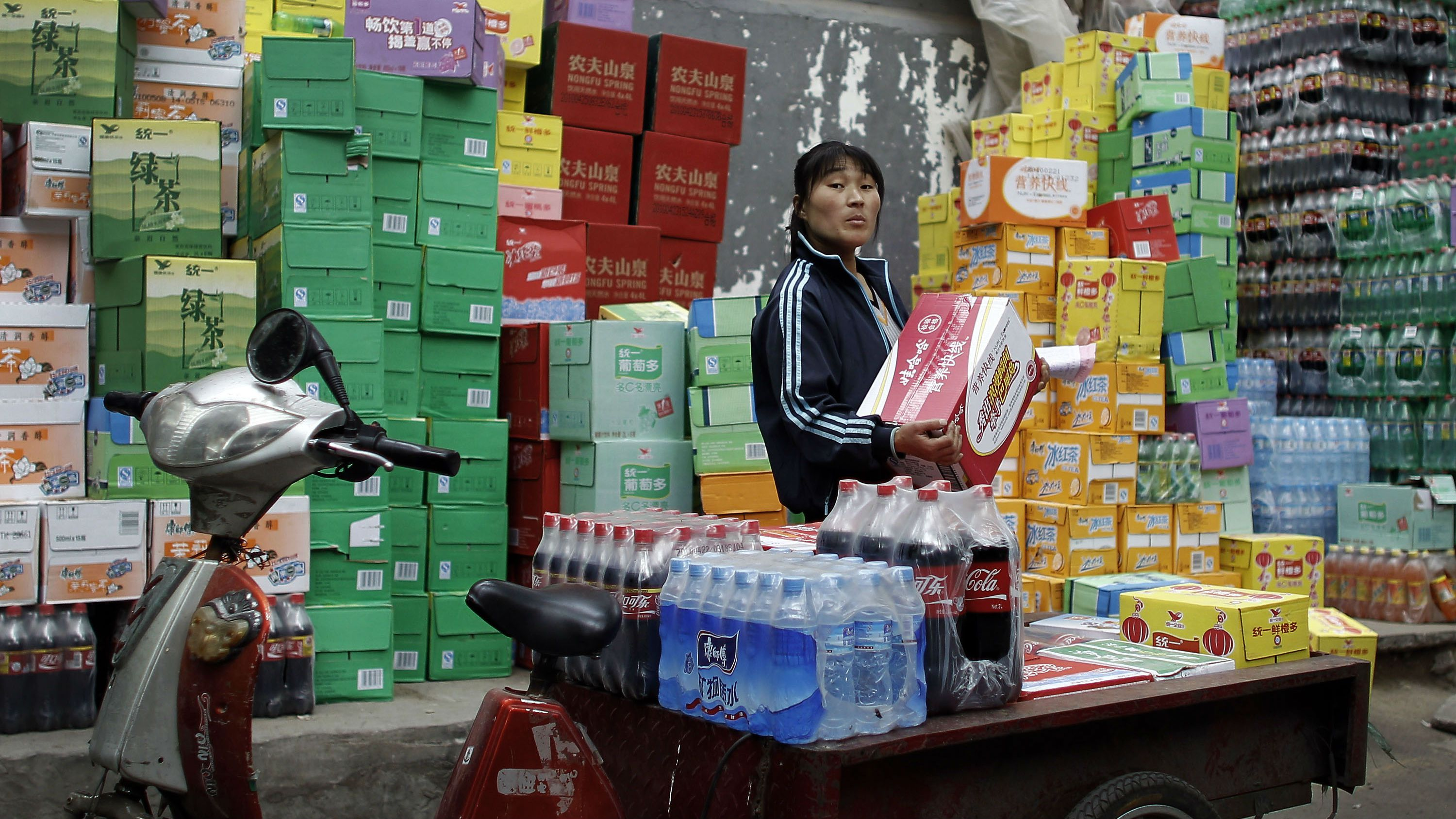 FILE - In this May 14, 2010 file photo, a woman loads beverages on her tri-cycle cart outside a store in Beijing. China's inflation rose in May amid signs its rebound from the global slump is slowing, adding to pressure on Beijing to keep growth on track and control politically sensitive prices. Consumer prices rose 3.1 percent from a year earlier, up from April's 2.8 percent rate, the National Bureau of Statistics said Friday, June 11, 2010. (AP Photo/Andy Wong, File)