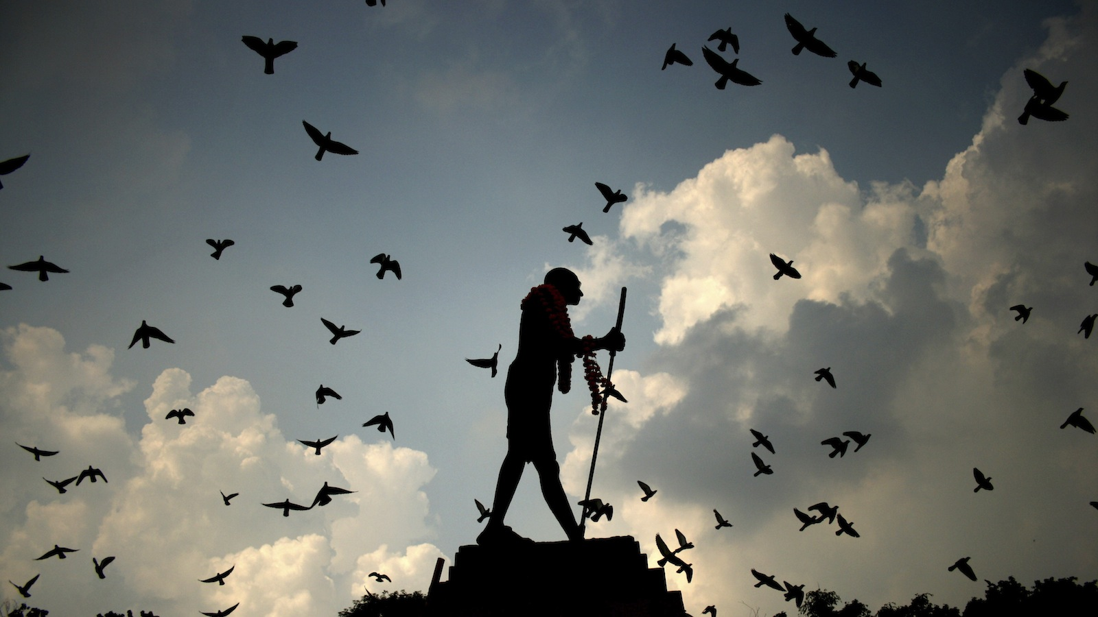Pigeons fly behind a silhouetted statue of Mahatma Gandhi adorned with garlands on Gandhi's birth anniversary in Amritsar, India Wednesday, Oct. 2, 2013. (AP Photo/Sanjeev Syal)