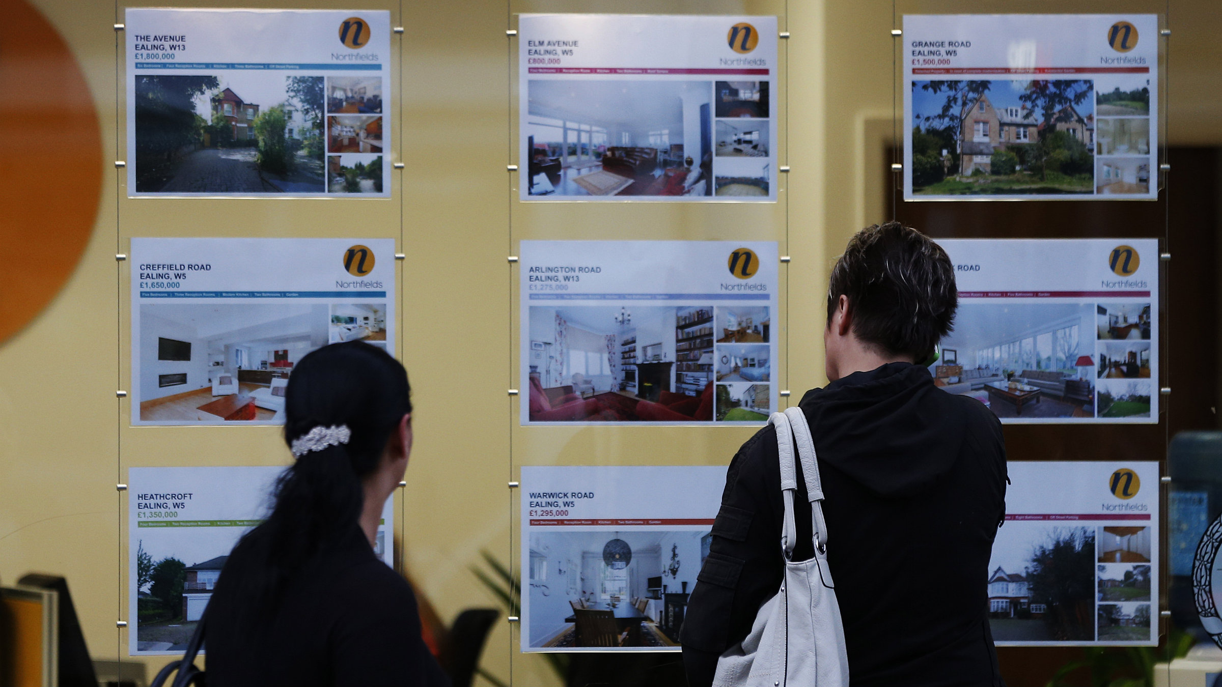 People look at houses for sale advertised in an estate agent's window in London.