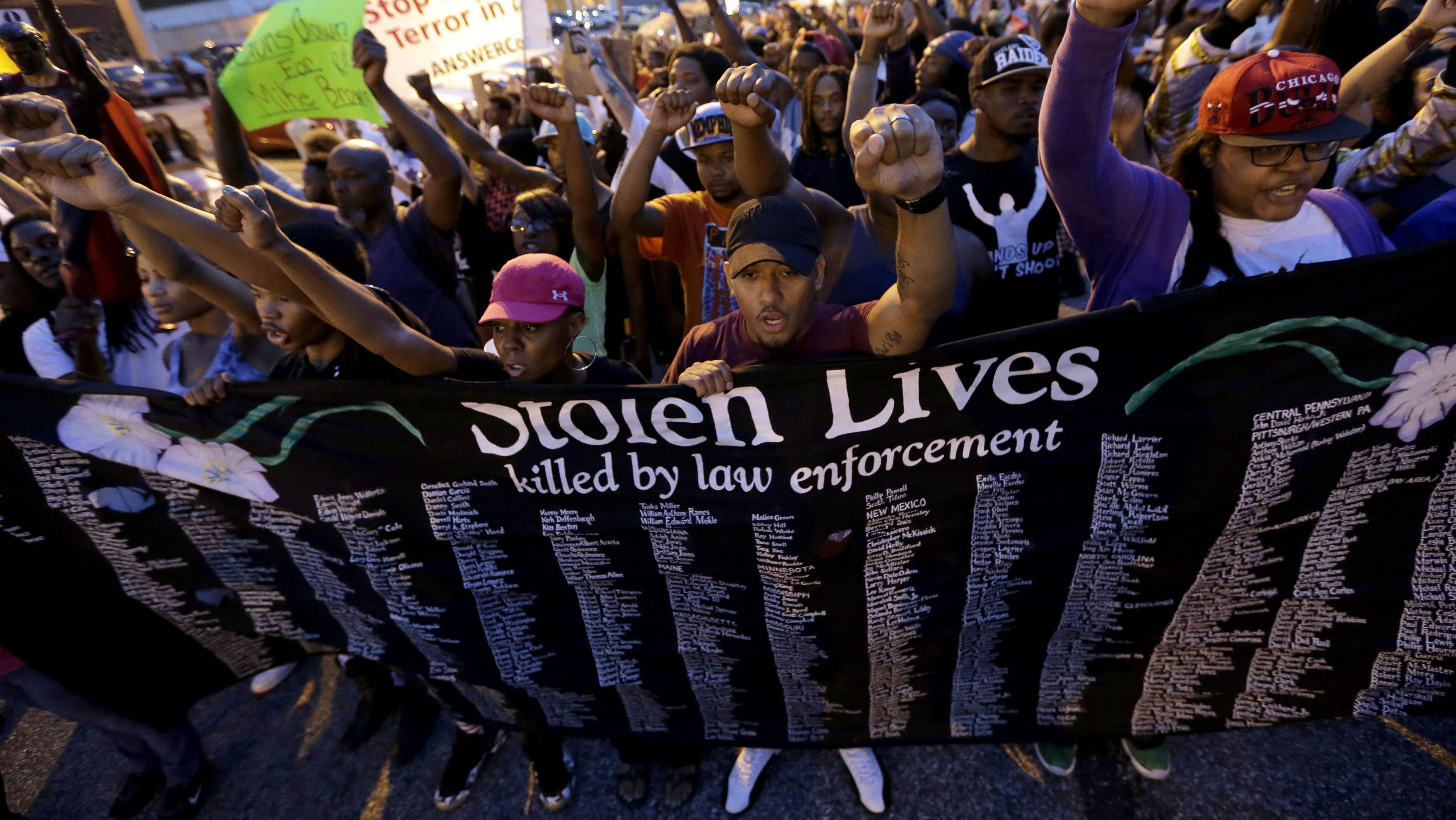 FILE - In this Aug. 16, 2014 file photo, people protest the police shooting death of Michael Brown in Ferguson, Mo. The response to Brown's death turned violent because of a convergence of factors, observers said. (AP Photo/Charlie Riedel, File)