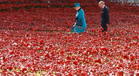Britain's Queen Elizabeth II, left, and the Duke of Edinburgh walk through the field of ceramic poppies at The Tower of London, Thursday, Oct. 16, 2014. The poppies are part of a ceramic poppy installation called 'Blood Swept Lands and Seas of Red' which marks the centenary of the outbreak of the First World War. (AP Photo/Kirsty Wigglesworth)