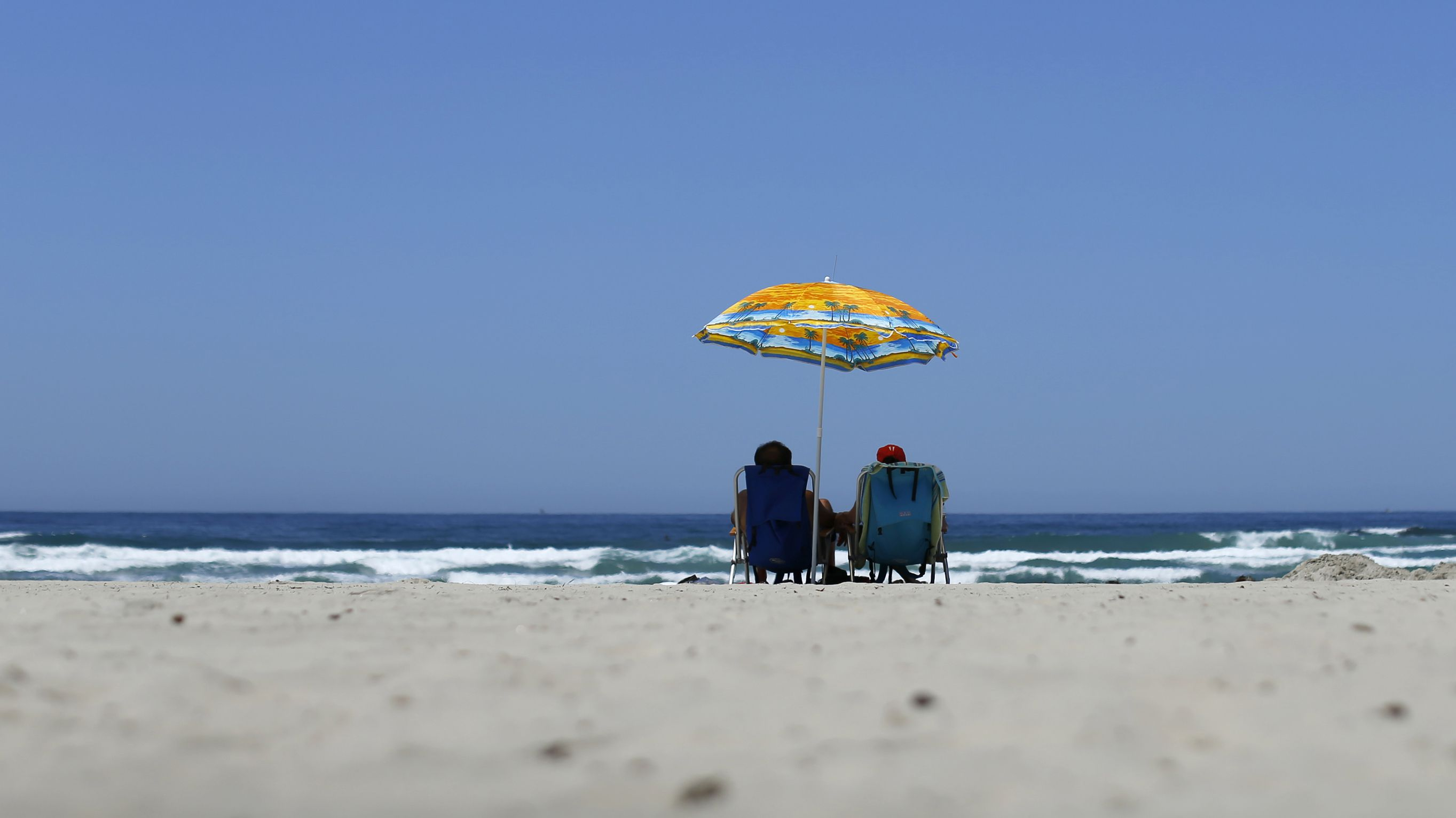 A couple sits under an umbrella for shade from the sun at the beach in La Jolla, California May 12, 2014. A high pressure system is expected to bring record breaking heat to Southern California over the next few days. REUTERS/Mike Blake
