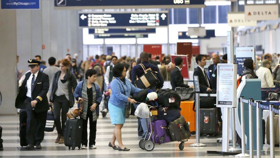 Passengers at O'Hare International Airport wait in a ticketing line Tuesday, May 13, 2014, in Chicago. Smoke in a regional radar facility forced a halt to all incoming and outgoing flights at both of Chicago's airports. The Federal Aviation Administration says all its personnel were evacuated from the Chicago Terminal Radar Approach Control, or TRACON, facility in suburban Elgin at around 11:30 a.m. Tuesday.(AP Photo/Charles Rex Arbogast)