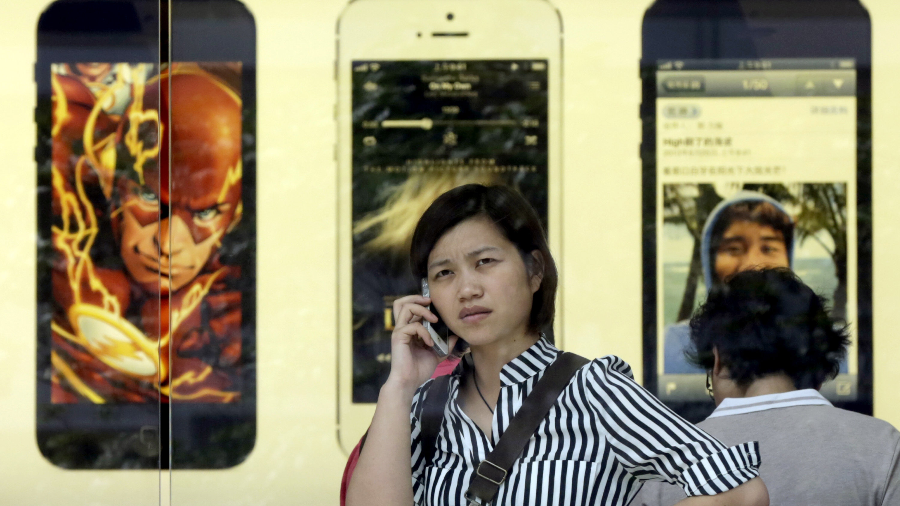 A woman talks on her iPhone at the Apple Store in Shanghai, China, Thursday, Sept. 12, 2013. (AP Photo/Eugene Hoshiko)