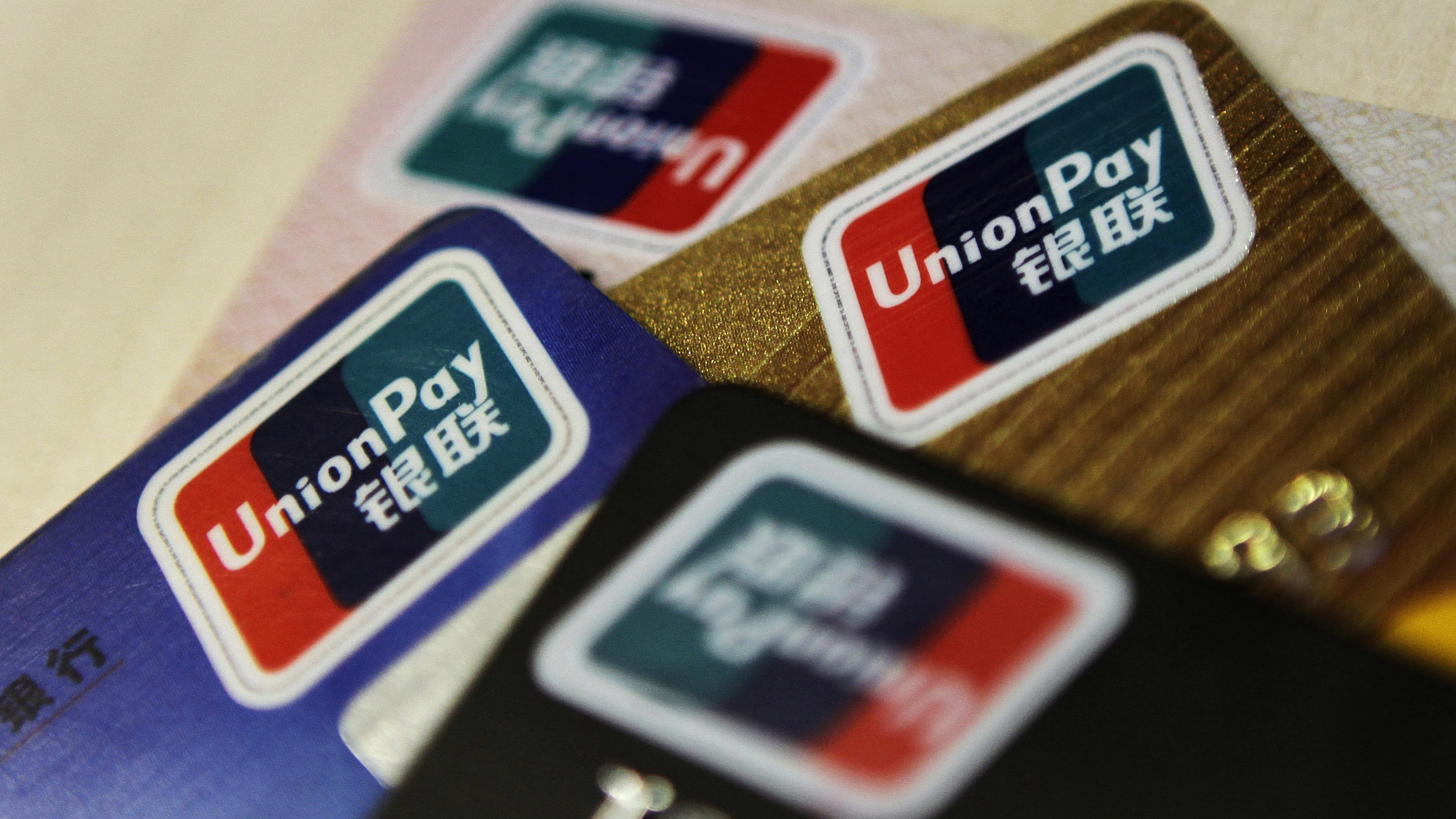 Logos of China UnionPay are seen on bank cards in this photo illustration taken in Beijing December 5, 2013. Picture taken December 5, 2013. To match Special Report CHINA-UNIONPAY/ REUTERS/Barry Huang (CHINA - Tags: POLITICS BUSINESS LOGO)