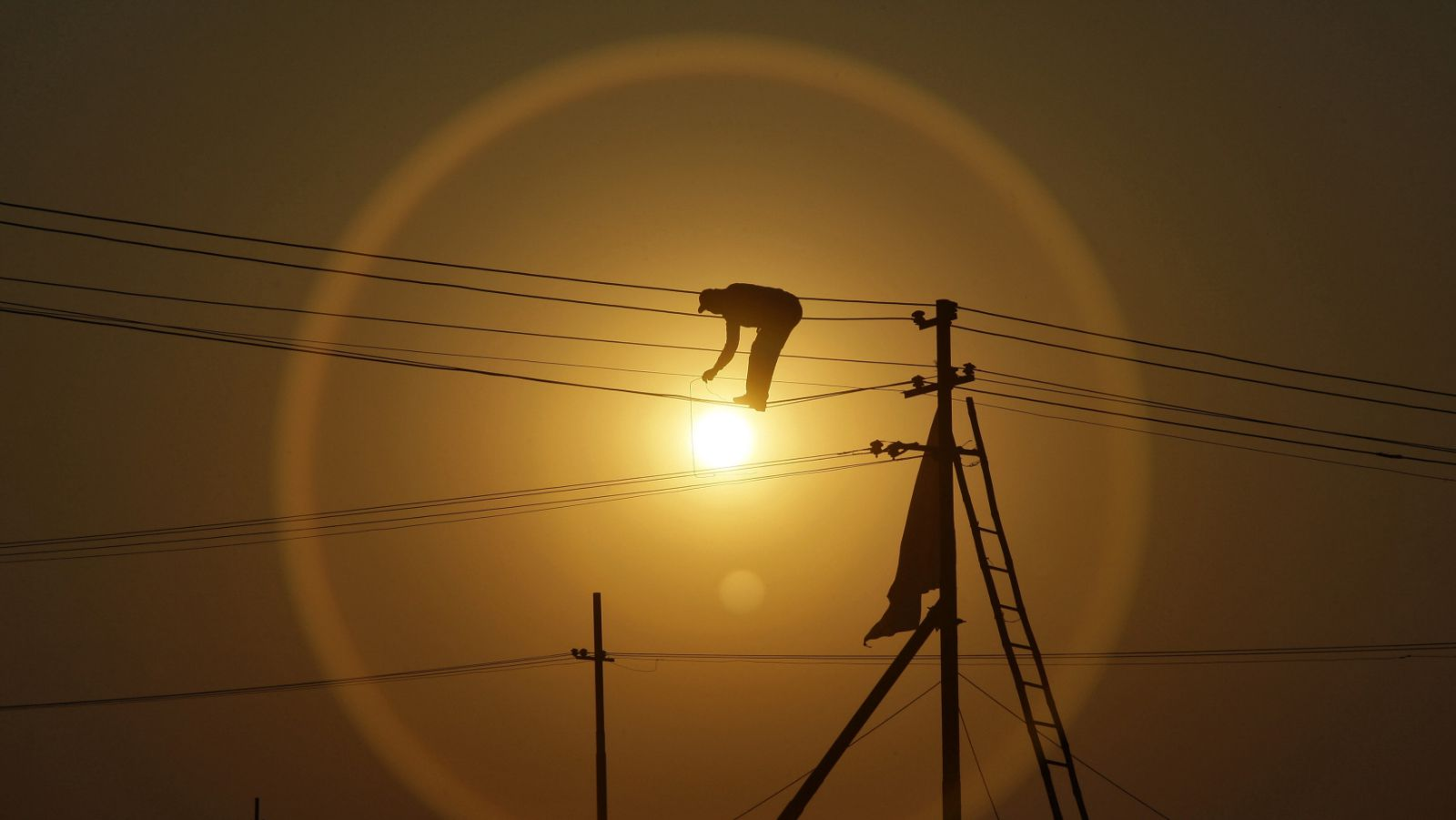 """An employee from the electricity board works on newly installed overhead power cables ahead of the """"Kumbh Mela"""", or Pitcher Festival, as the sun sets in the northern Indian city of Allahabad December 7, 2012."""
