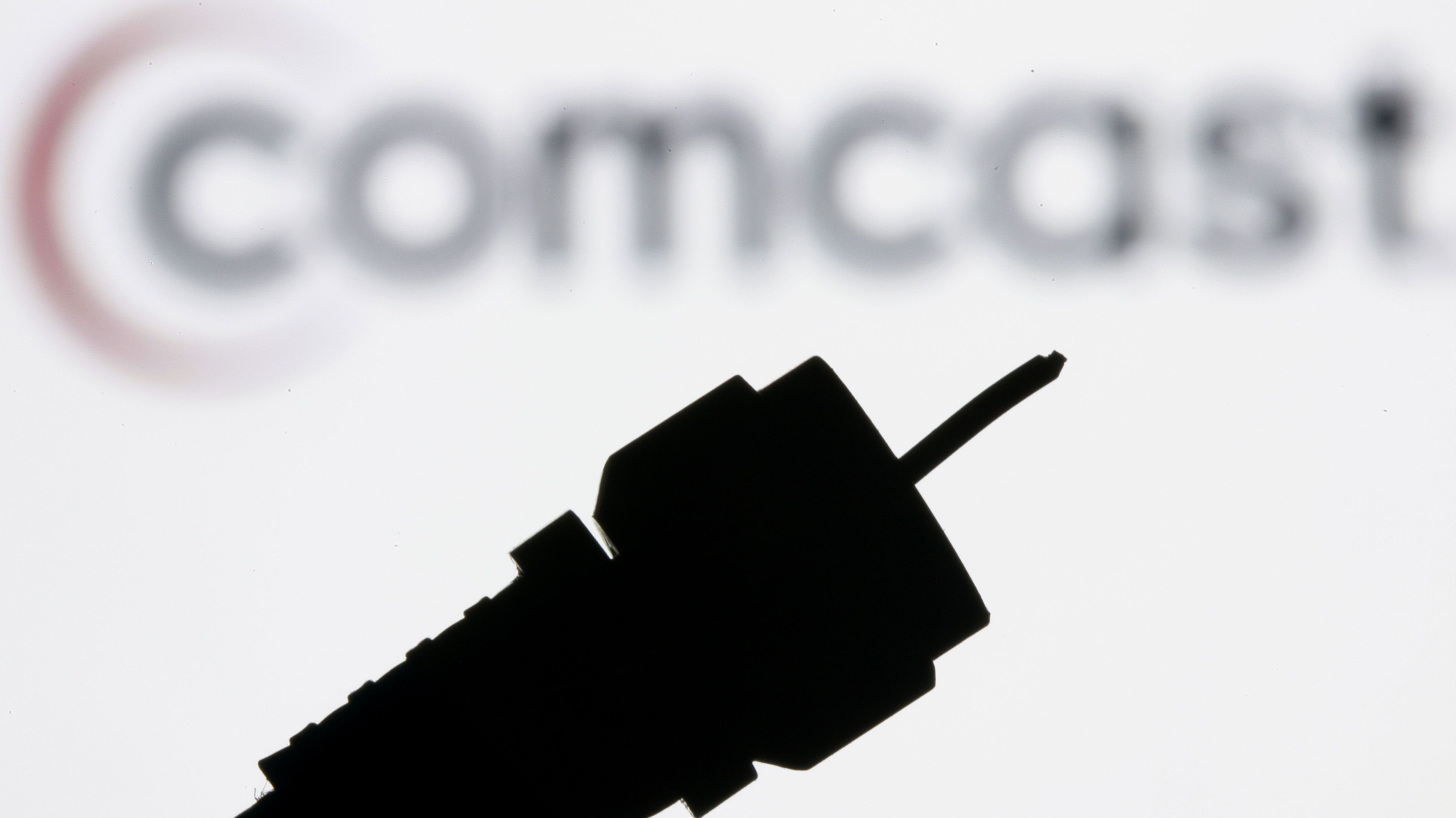 A silhouetted coaxial cable is photographed with the Comcast Corp. logo in the background.