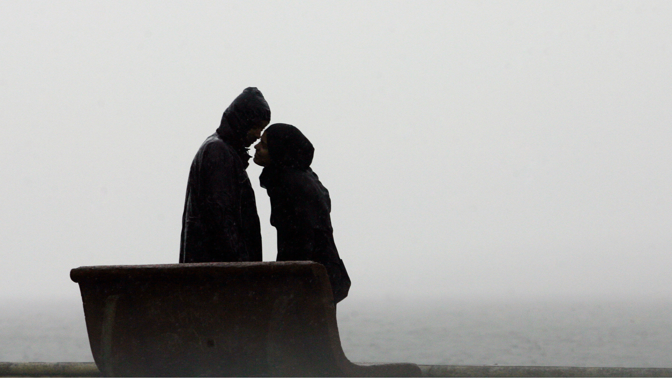 A couple kisses at a sea front off the coast of the Arabian Sea in Mumbai November 11, 2009.
